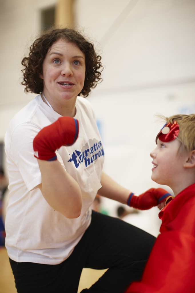 Jess Thom talking to a child at event in 2010, she is mid tic and is wearing padded red boxing gloves. The child is dressed as a superhero.