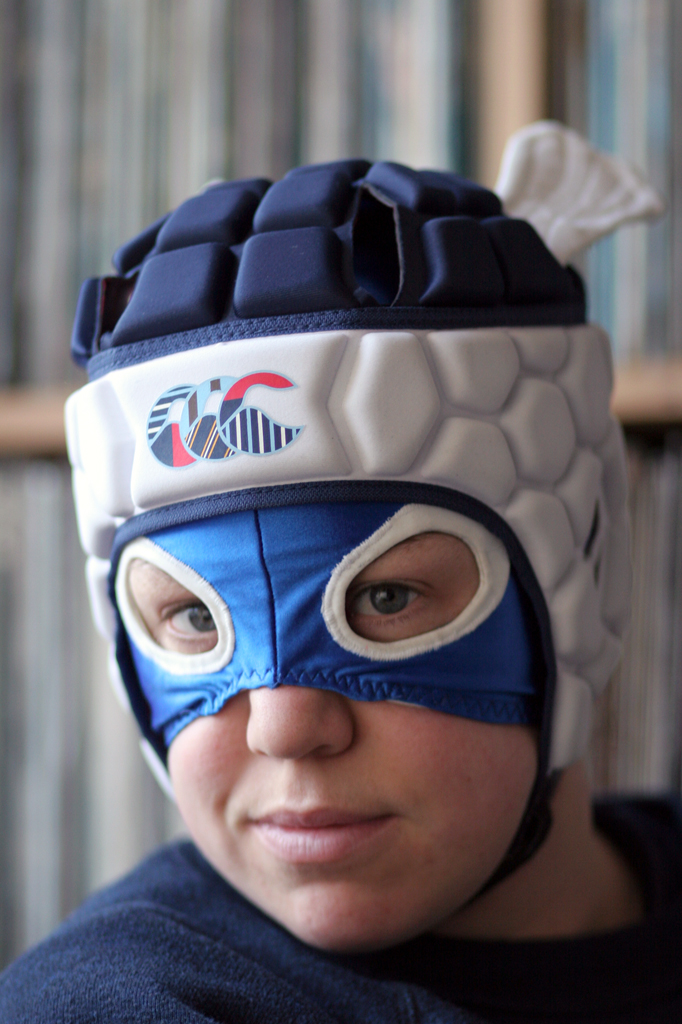 Photograph of Touretteshero, a white woman with brown curly hair, sporting a dark blue and white dog-eared padded trapper hat as well as a blue mask covering her forehead up to her nose with large holes for her eyes.