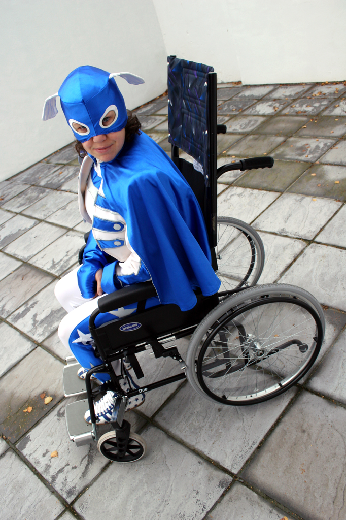 A photo of Touretteshero in full blue and white superhero costume, sitting in a black wheelchair with a high head-height backrest, large grey wheels and large grey footrests.