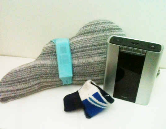 A wireless doorbell that Touretteshero uses as a portable alarm. The bush buttons for the alarm have been strapped onto a cushion and inserted into a sweatband so they can be reached easily.