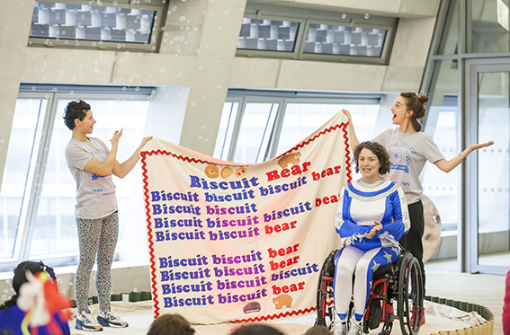 An image from Adventures in Biscuit Land at Tate Modern, Touretteshero and Chopin are on stage holding up a fabric banner with the lyrics for a song called Biscuit Bear