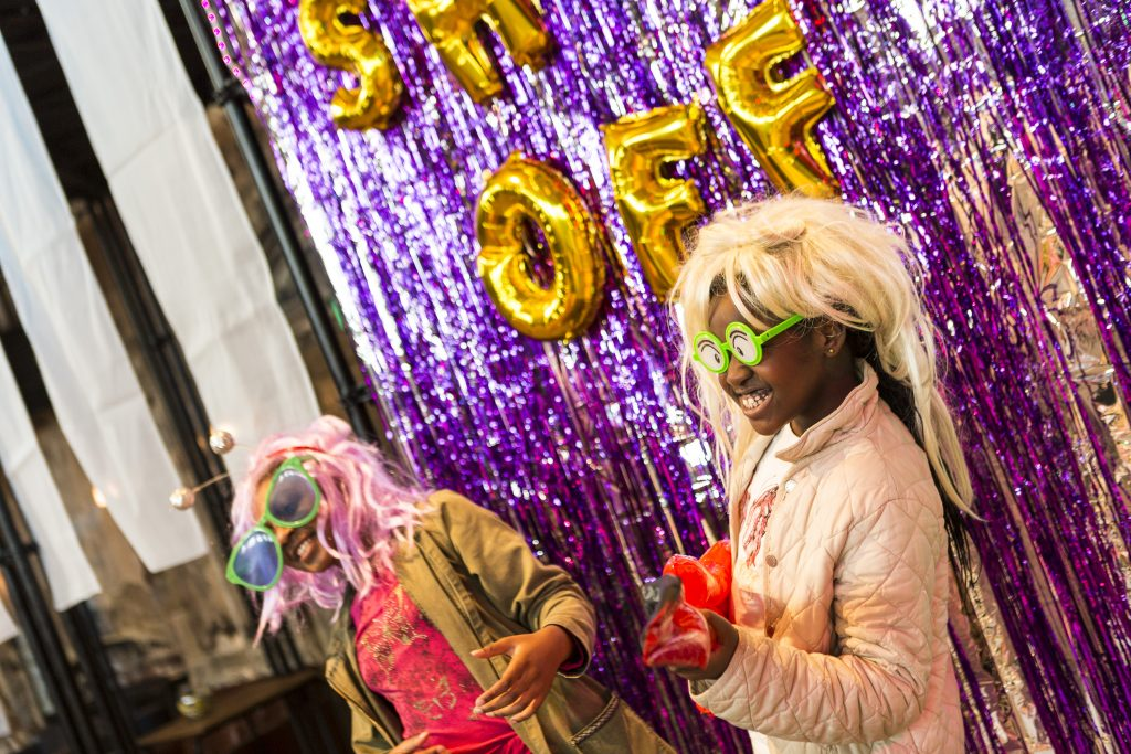 A photo of two smiling children in wigs and colourful glasses in front of a purple glitter curtain. Balloon letters spell out Show Off!