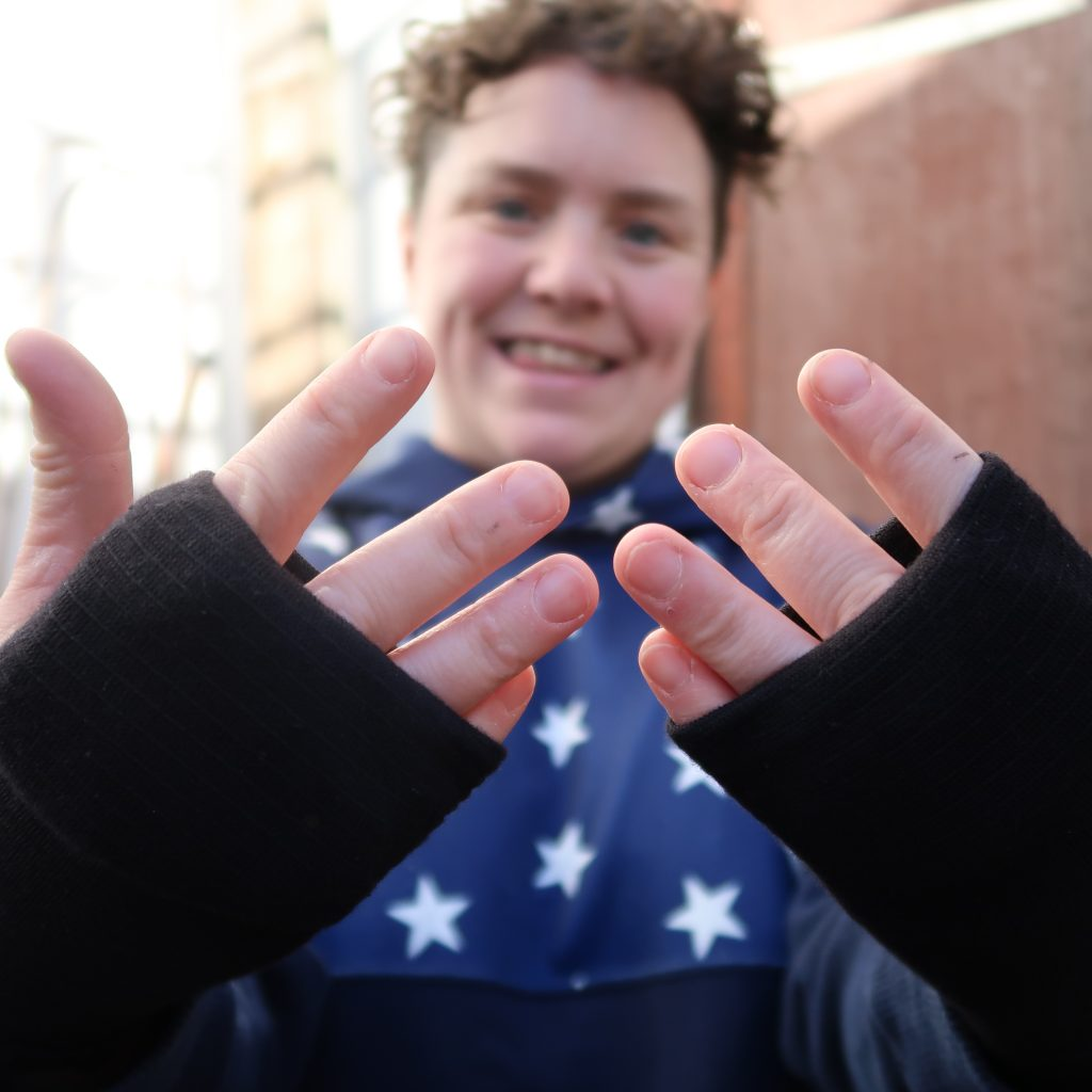 A picture of Jess Thom a white woman with short curly brown hair smiles at the camera and holds out her hands towards the viewer. She is wearing a pair of padded gloves made using black tube-grip bandages.