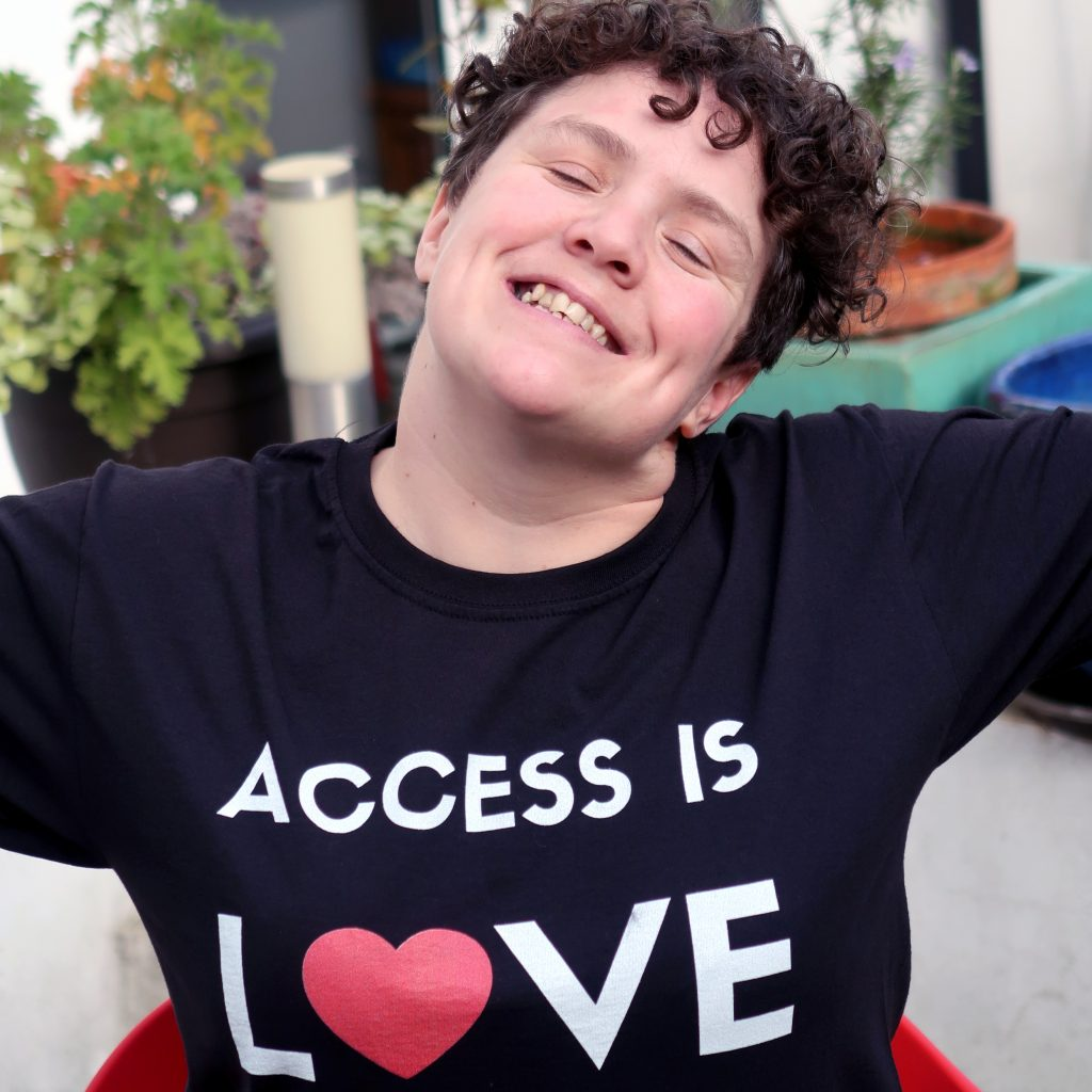 Jess Thom, a white woman with short curly hair, smiles and raises her arms in the air. She's wearing a long-sleeved black t-shirt with the text 'Access Is Love' written on it, and the 'o' in 'love' is a heart.