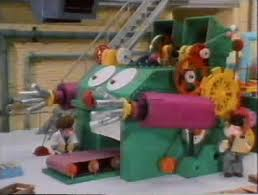 A green and pink animated machine with big eyes. This is Bertha the main character of a TV series from the 1980's.