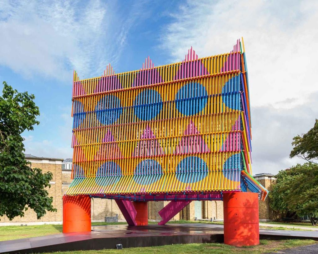 A colourful temporary modern pavilion made out of wooden slats. The structure sits on four red pillars and is bright yellow with blue and pink geometric shapes painted on the outside. The pavilion sits in the grounds of Dulwich Picture Gallery which is visible behind it.