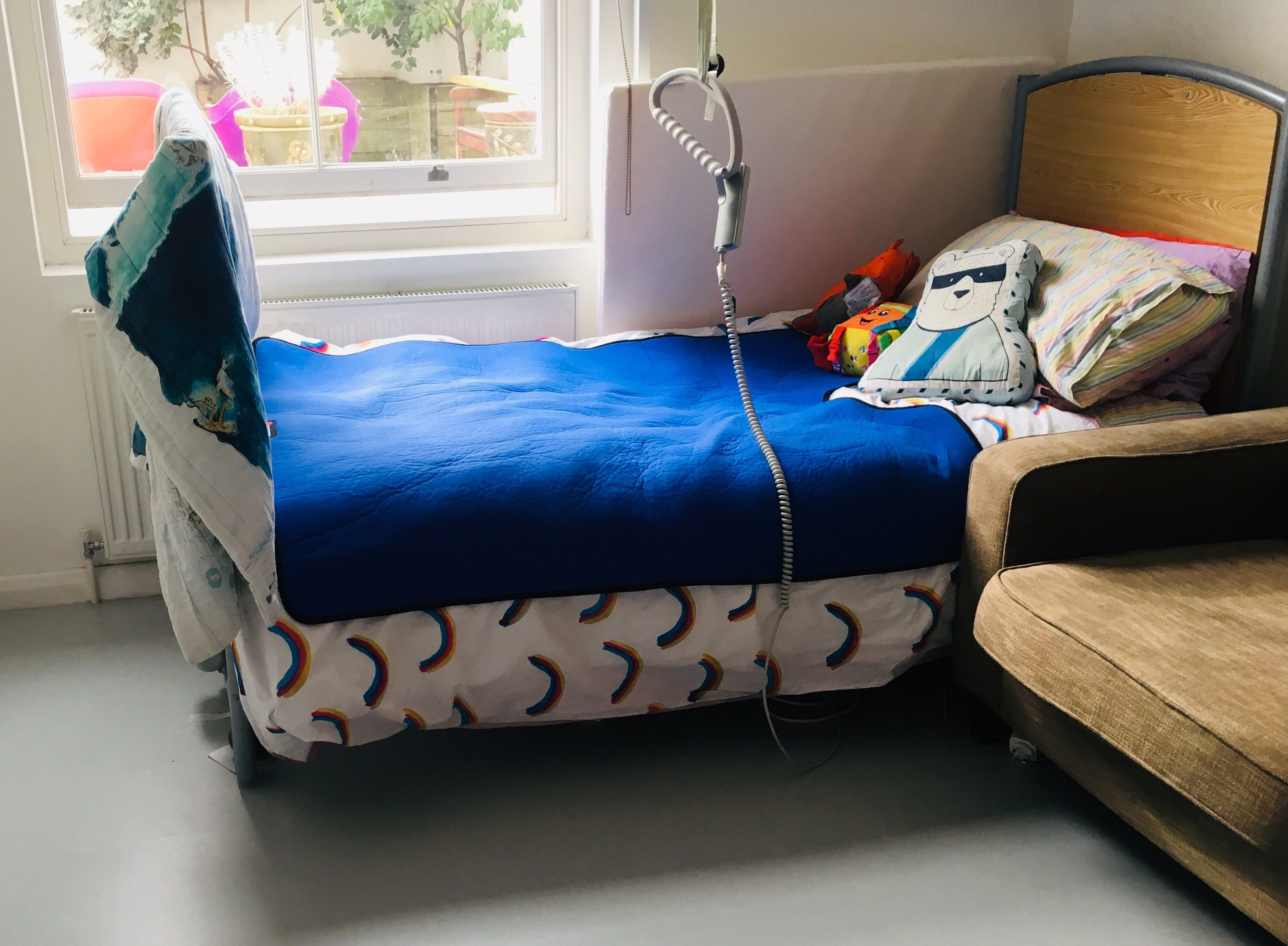 Photo of Touretteshero's profiling bed along with royal blue weighted blanket on top. The bed is next to a window looking out into a garden.