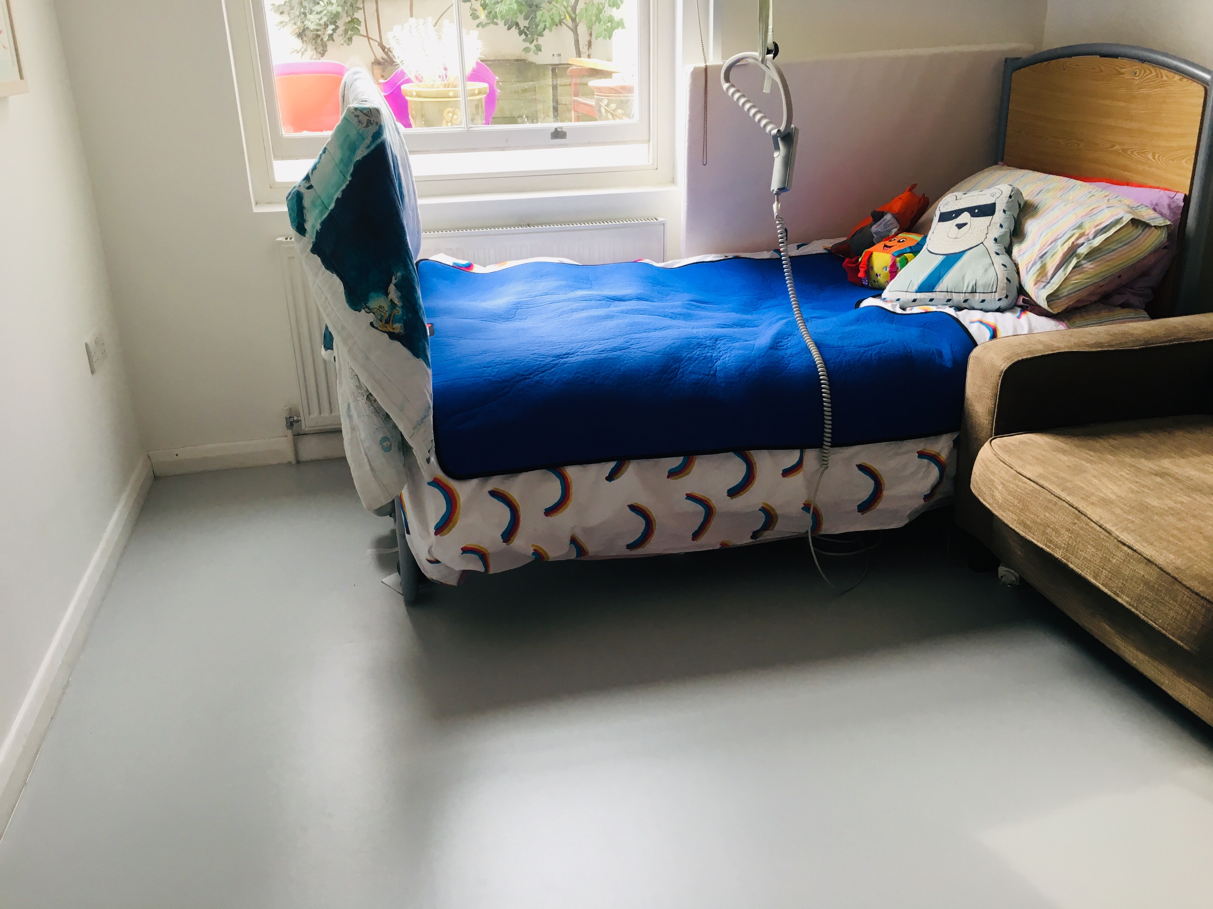 Photo of new grey lino floors with Touretteshero's bed under a big bright sash window looking into a garden where several plant pots are visible. Touretteshero's bedding has rainbows on it and