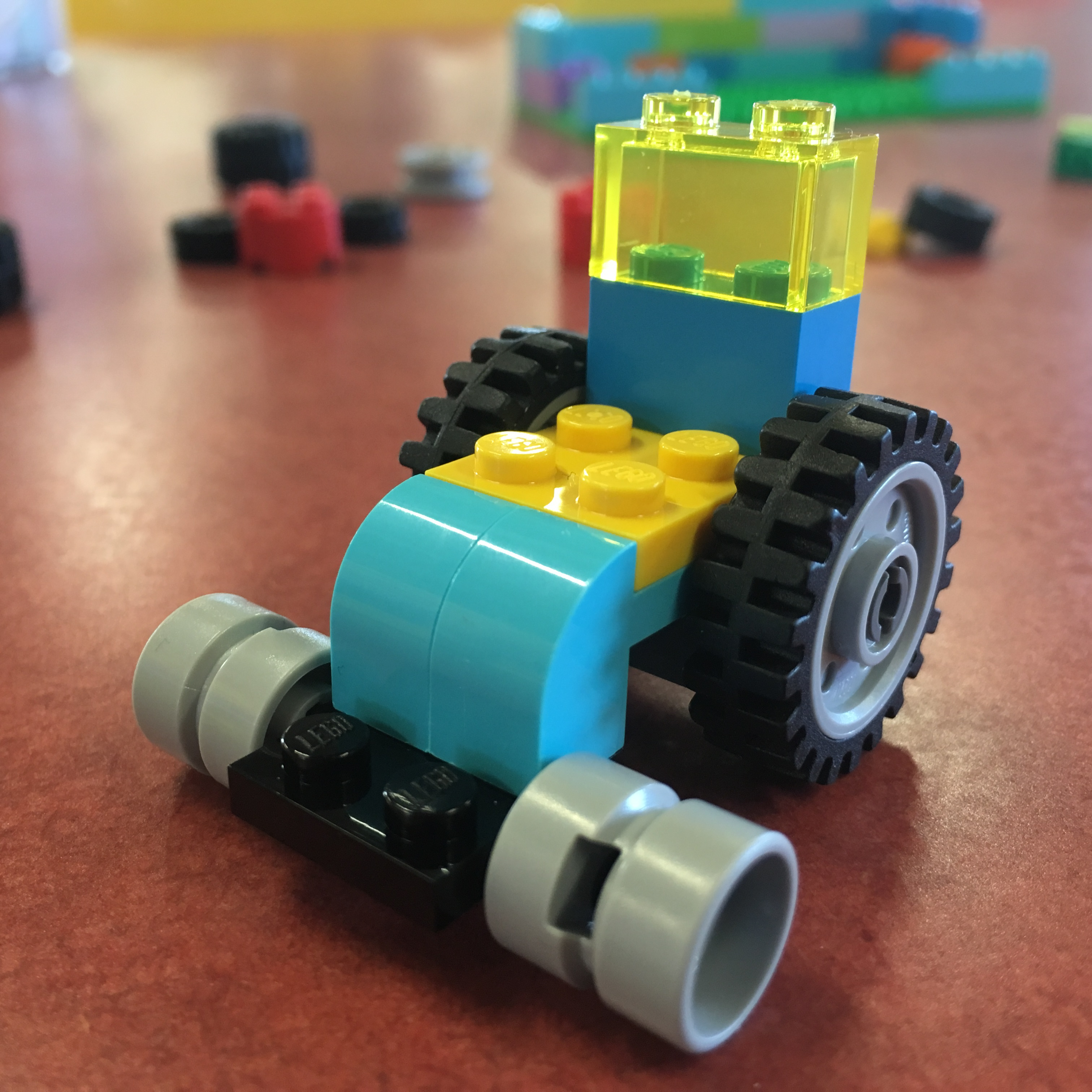 Photograph of Lego Wheelchair made by Touretteshero. It is made using colourful translucent green, baby blue, yellow and blue blocks with big jumbo wheels and wide castor wheels
