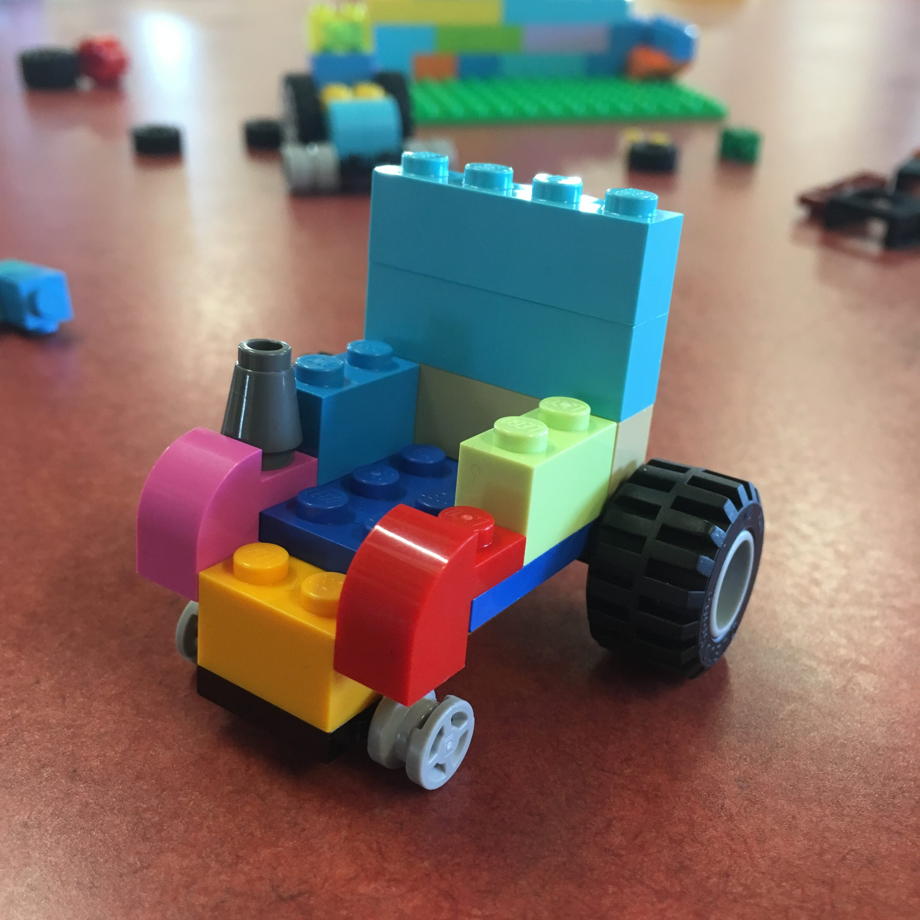 Photograph of Lego Wheelchair made by Touretteshero. It is made using colourful red, pink, green, teal, orange and blue blocks with big jumbo wheels and little castor wheels