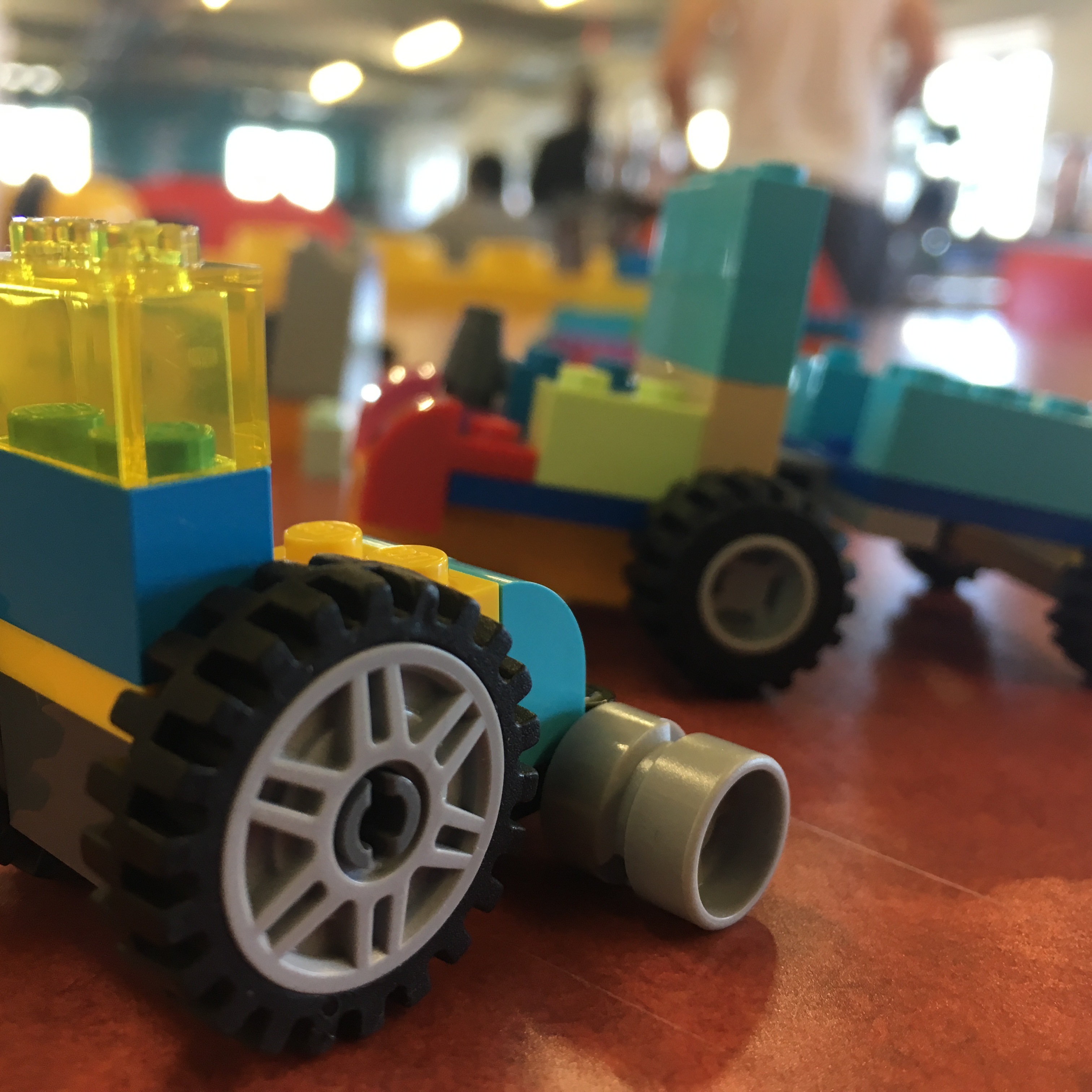 Photograph of Lego Wheelchair made by Touretteshero. It is made using colourful translucent green, baby blue, yellow and blue blocks with big jumbo wheels and wide castor wheels. Other lego wheelchairs are visible in the background.