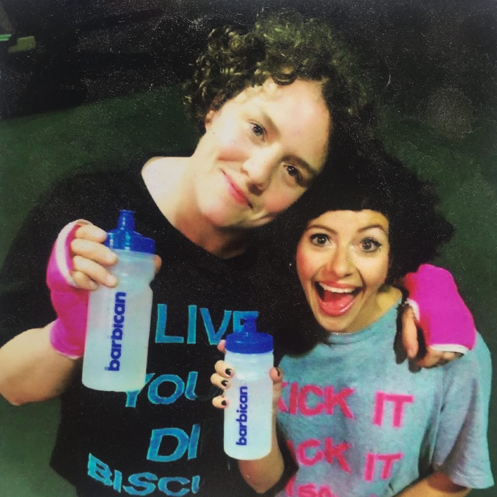 "Photograph of two friends Touretteshero and Chopin. Touretteshero has short curly brown hair and pink gloves on and is wearing a black t-shirt with blue text that says ""Live Young Die Biscuity"" She is smiling and has her arm around Chopin who is also smiling. Chopin is wearing a grey shirt with pink text that says ""Fuck it"" They are both holding Barbican branded water bottles."
