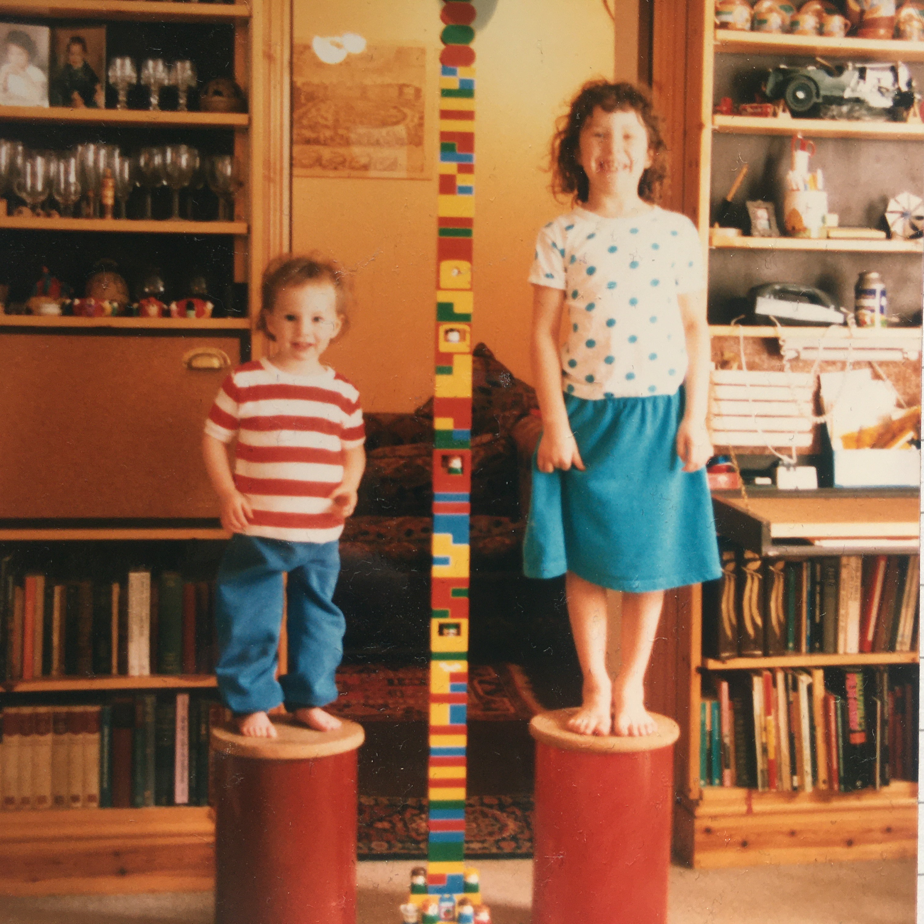 An old photography of Touretteshero and Fat Sister as children. Touretteshero is wearing a blue skirt and white top with black polkadot and is standing on an upturned red barrel and is smiling widely. Fat Sister is wearing a red and white striped t shirt and blue jeans and is also standing on an upturned red barrel on the left. In between the sisters is an enormous colourful duplo tower taller than both of then and the length of the height of the photograph. There are bookcases on either side of the sisters.