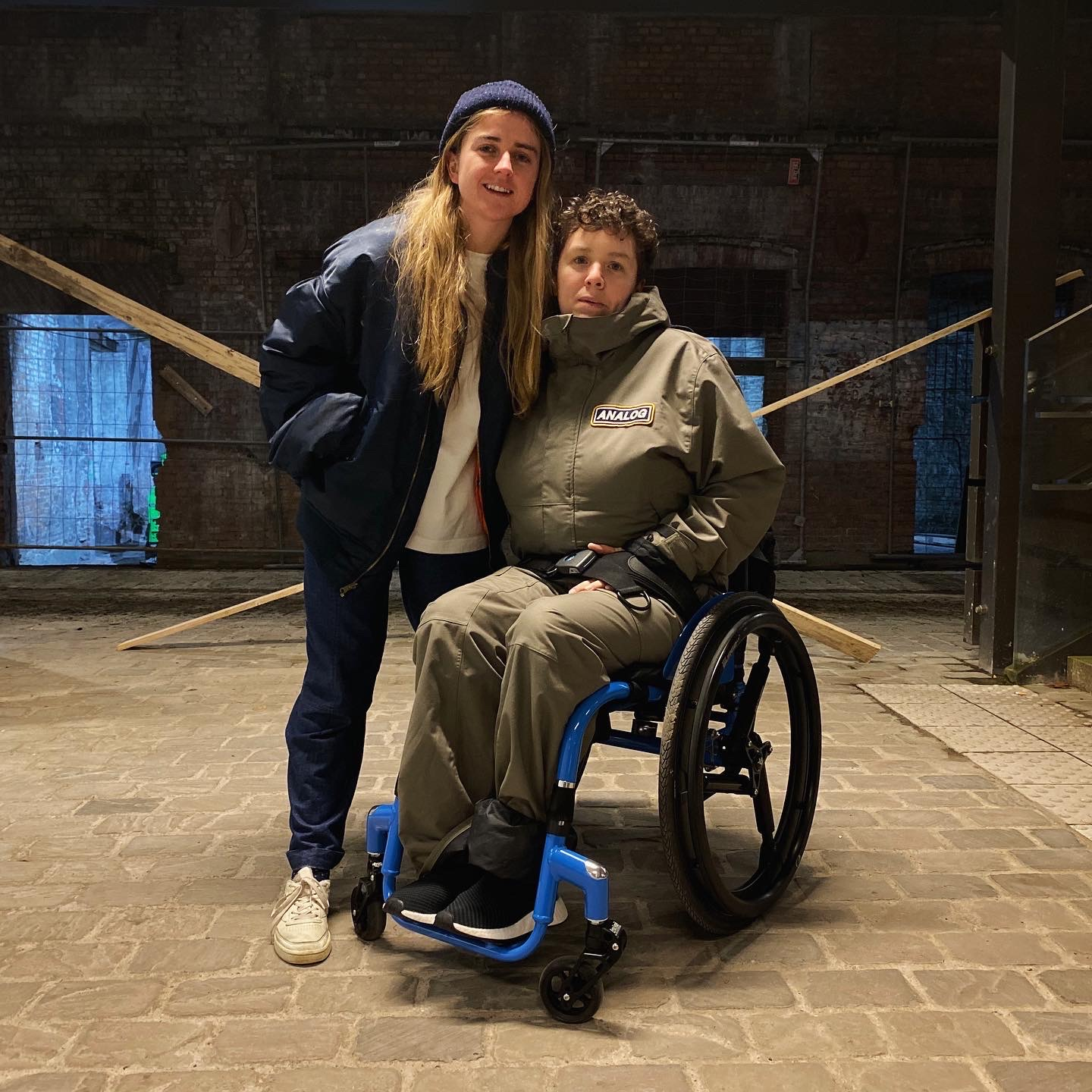 Touretteshero and Claire together on a recent trip to Ghent in Belgium. Touretteshero has short curly brown hair and is in a green khaki snow suit and sitting in her new RGK wheelchair. It is blue with black frogs legs castor and black shock absorbing wheels. Claire is wearing a navy wool speckled beanie and navy air force one jacket and blue trousers.