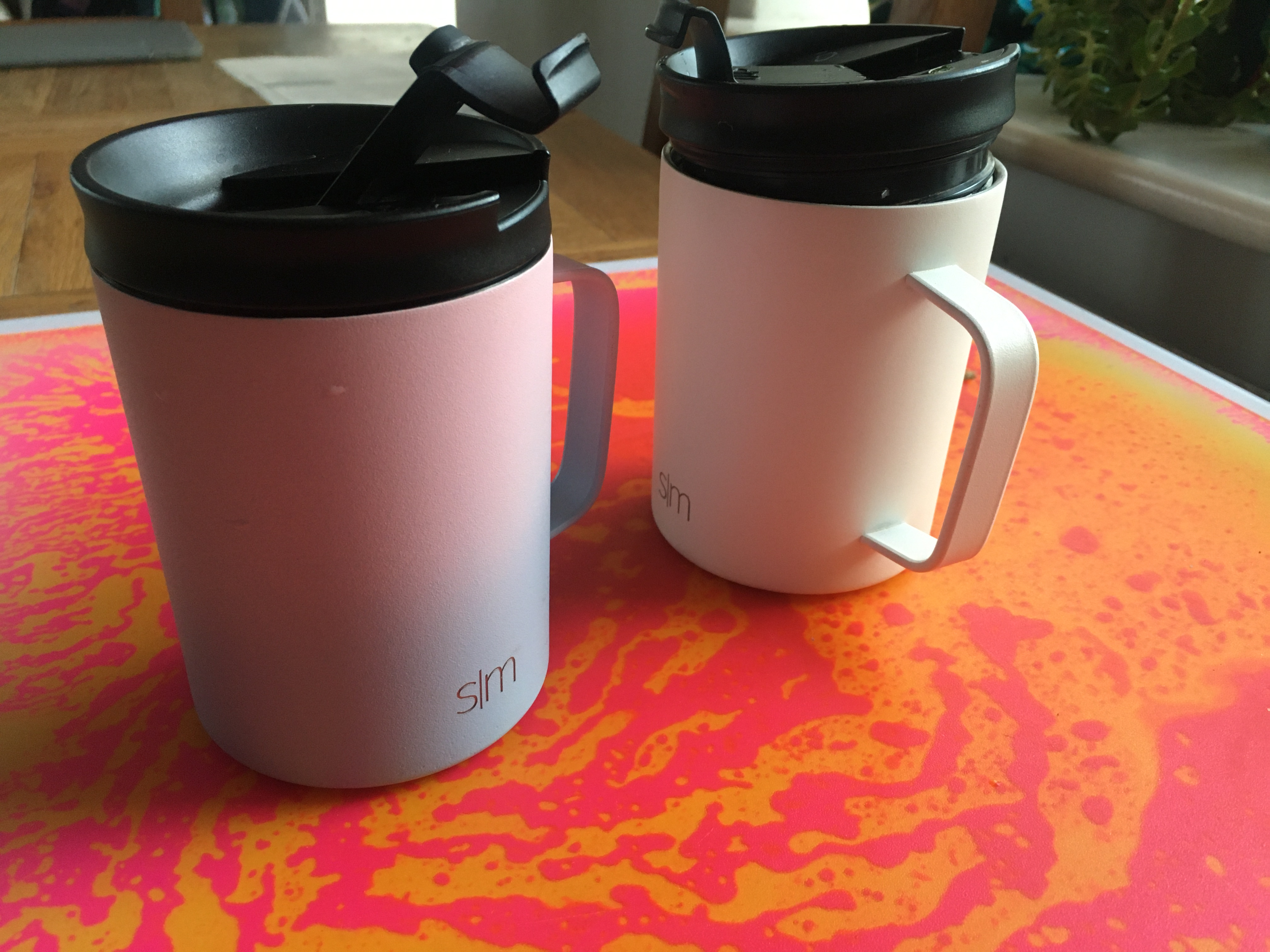 photo of two lidded cups on a fluorescent orange and pink table. One cup is pink and blue gradient with a black lid. The other cup is white with a black lid.