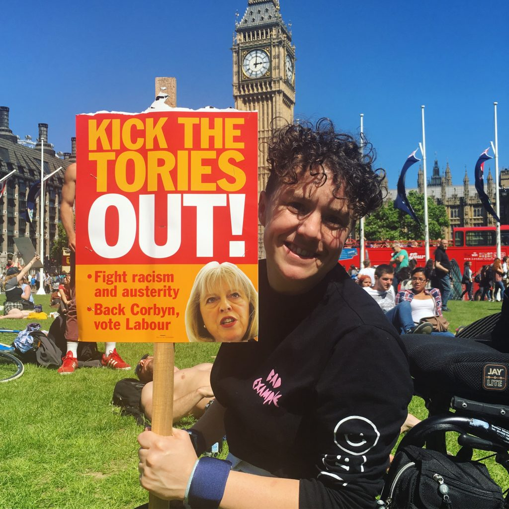 Jess Thom holds a Kick The Tories Out placard outside Westminster.