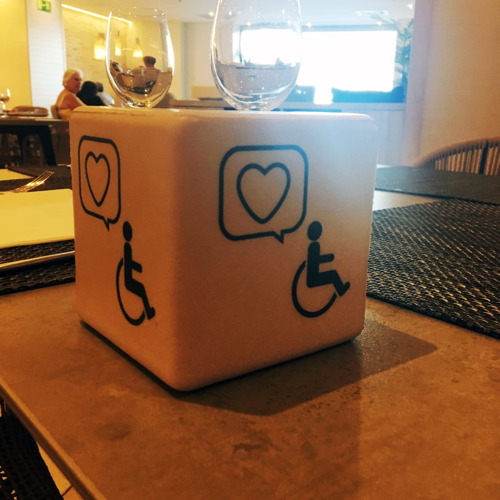 A white cube sits on a dining room table. A blue symbol of a wheelchair is printed on each side of the cube along with a speech bubble containing a heart.