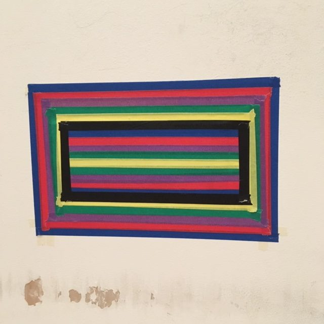 A photograph of the wall in Touretteshero's bathroom showing a brightly coloured rectangle of fluorescent stripes made using different coloured masking tape. This is completely covering a hole made by Touretteshero's foot.