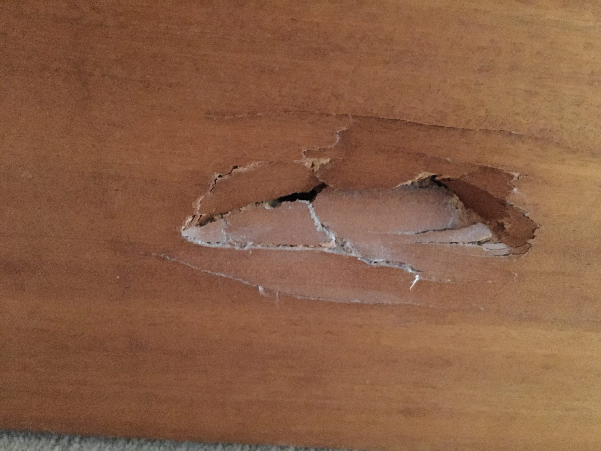 Image shows a close up photograph of a hole made by Touretteshero's foot on the wooden footboard of her bed.