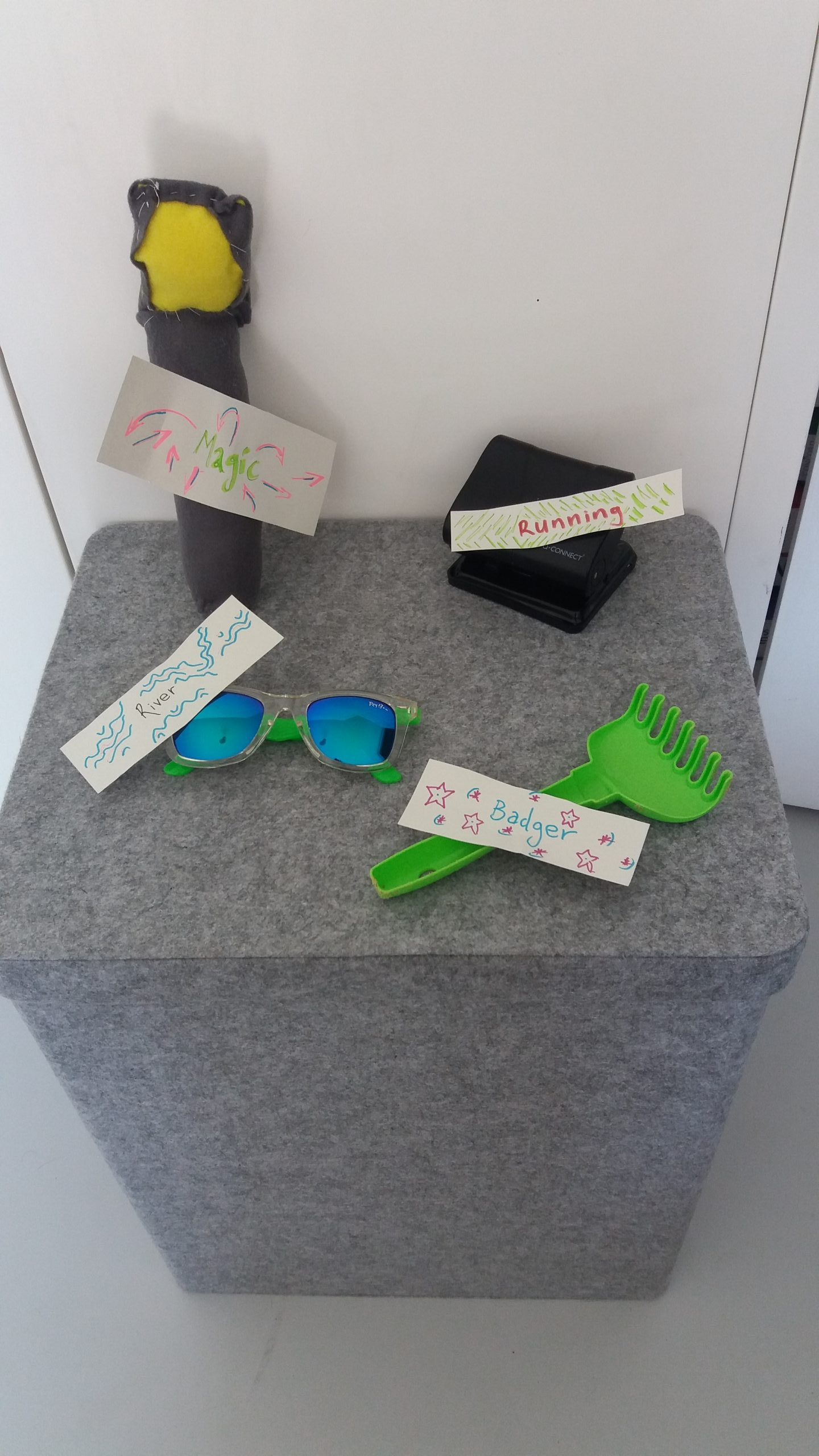 Photograph of a group of labelled objects on a grey wooden box. The objects include a felt lamppost labelled Magic, a small green plastic rake labelled Badger, a black plastic hole puncher labelled Running, Blue mirror lenses sunglasses labelled River