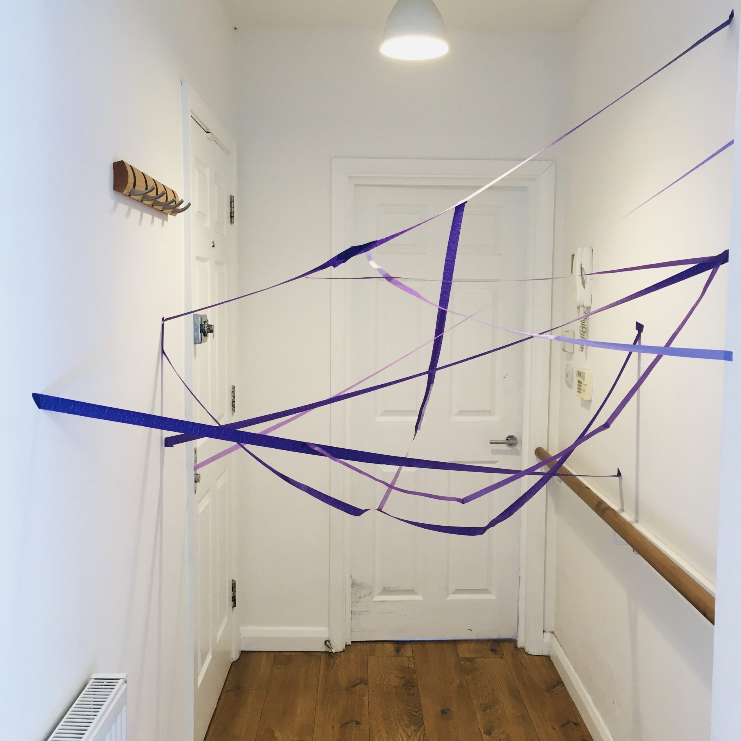 A photograph of a tangle maze in a white hallway with wooden floors. Brightly coloured Purple masking tape criss crosses throughout the corridor acting as a tangle maze of obstacles!