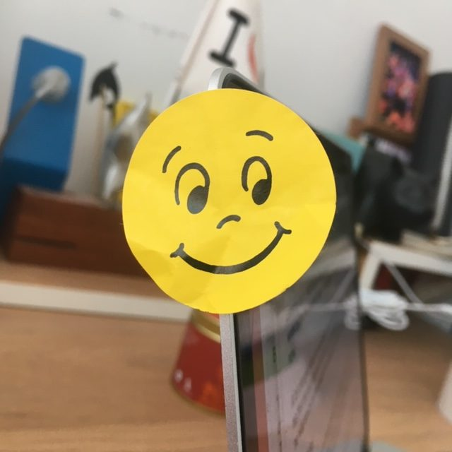 A smiley yellow sticker photographed close up a desk and items of stationary are visible in the background