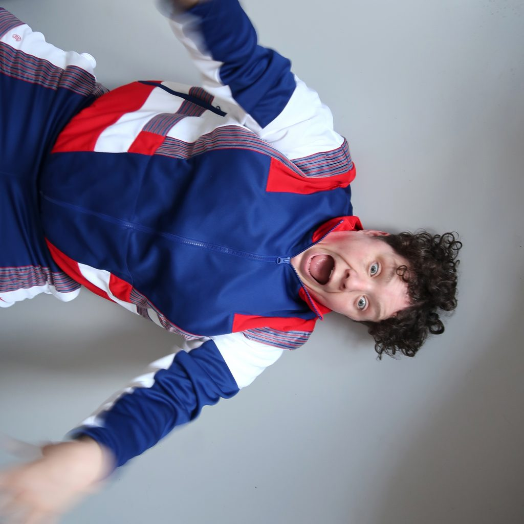 Touretteshero - a white woman in her late thirties is wearing a blue, white and red tracksuit. The background behind her is solid grey, Touretteshero is waving her arms in excitement.