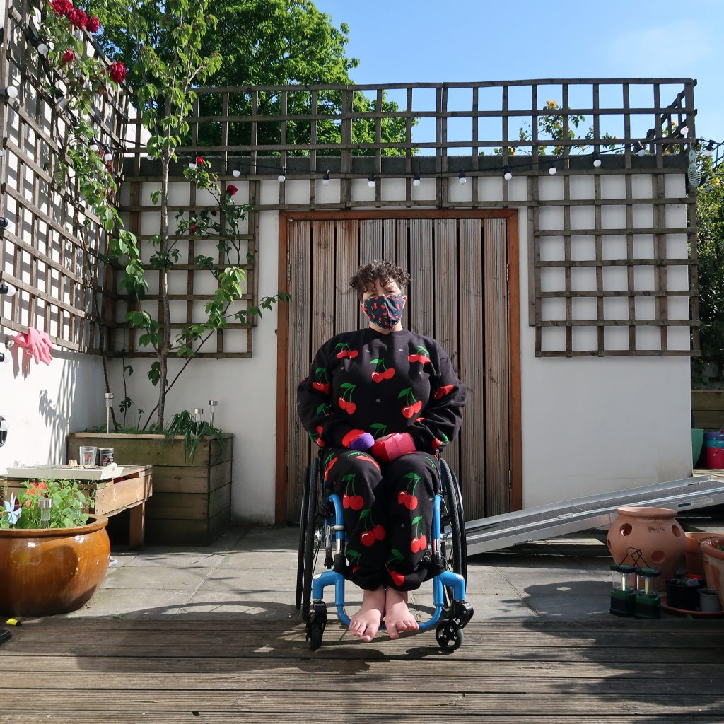 Image shows Touretteshero in her garden. Plants and roses on trellis' adorn the background. In the centre of the image Touretteshero is wearing a matching black tracksuit with a cherry pattern. She is wearing a matching black face mask with a cherry pattern.