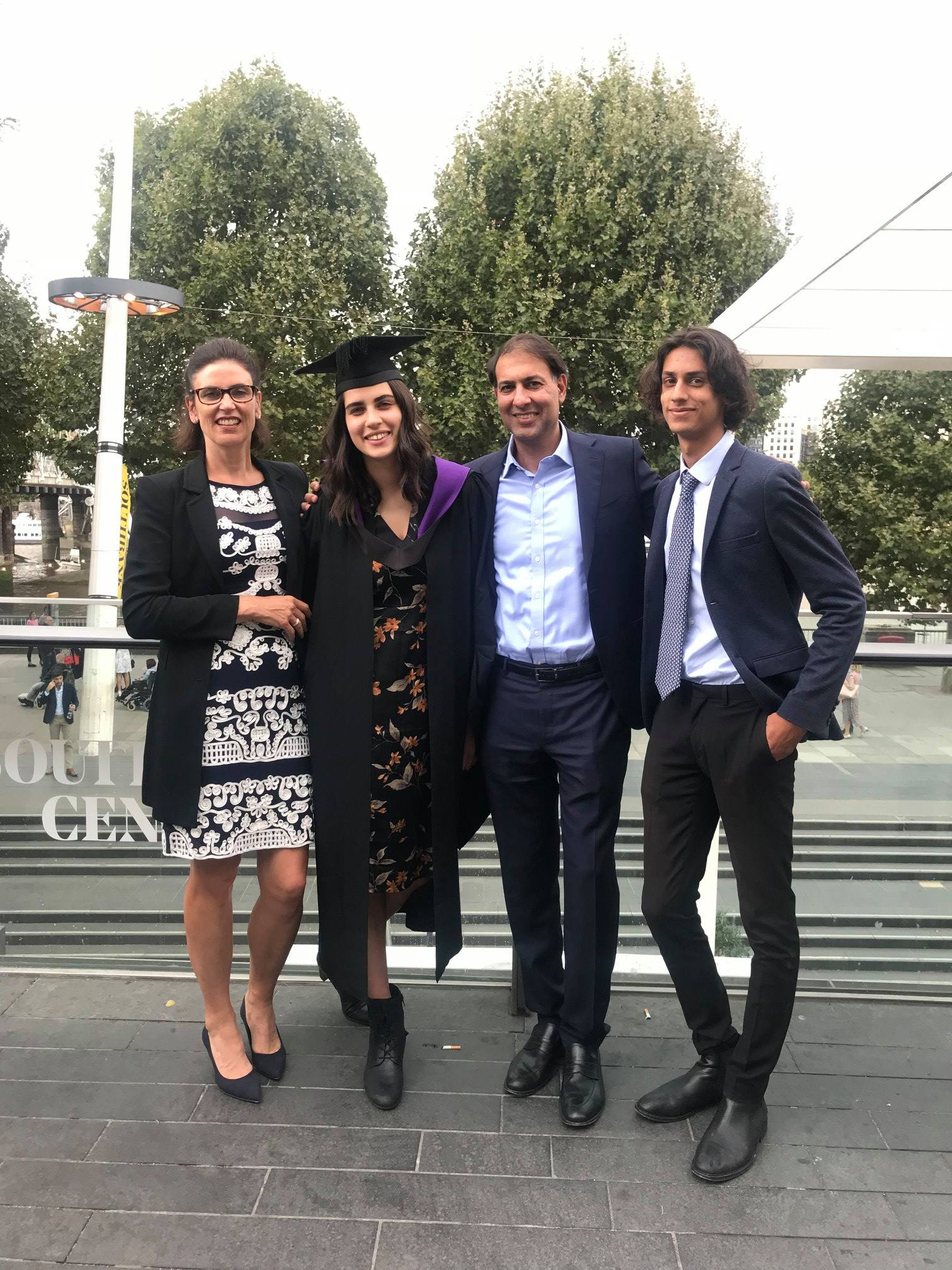 Serena and her parents and younger brother - a family of mixed south Asian and European heritage pose for a happy picture in formal attire. Serena is wearing a cap and gown for her university graduation ceremony.