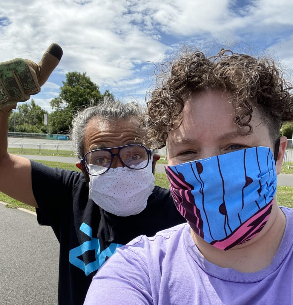A photo of Jess Thom a white woman and her Personal Assistant Erik a brown man out and about on a sunny day. Both are wearing masks and looking at the camera - Erik is doing a thumbs up gesture.