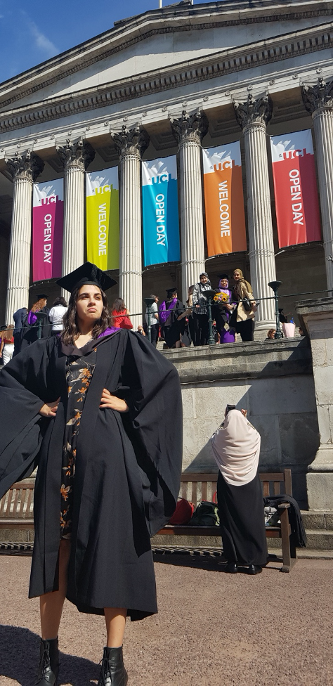 Serena, just before her BSc graduation from UCL in September 2018. She is wearing a black graduation cap and gown and is standing in front of UCL with both hands on her hips. She is looking out into the distance with an upset look on her face. Her MSc graduation, originally scheduled for this week, has been cancelled due to COVID-19.