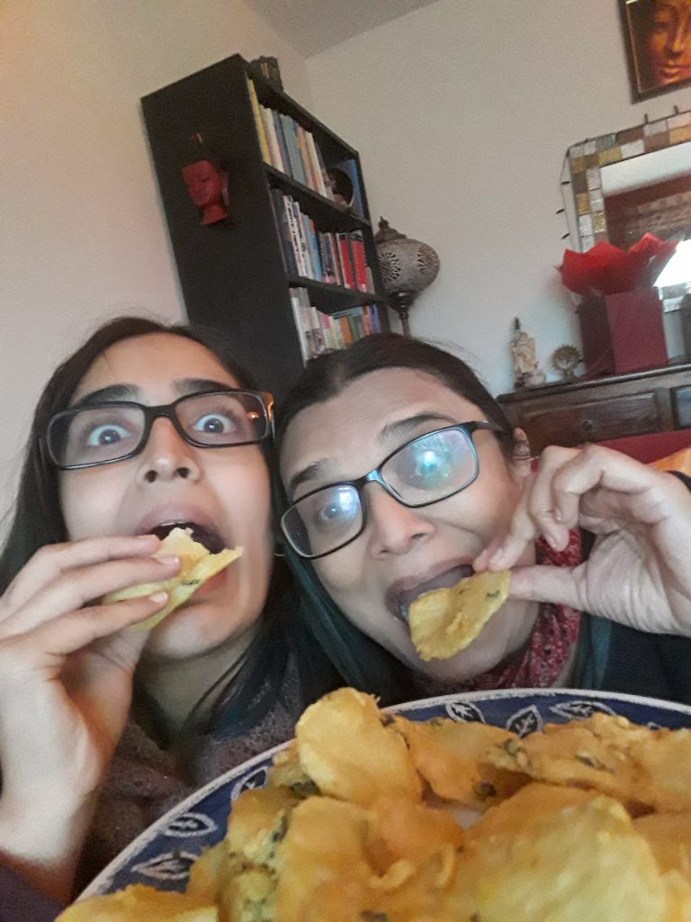 The image is of Yaska and her mother eating their favourite friend food (Maru bhajias). They are making funny, excited faces.