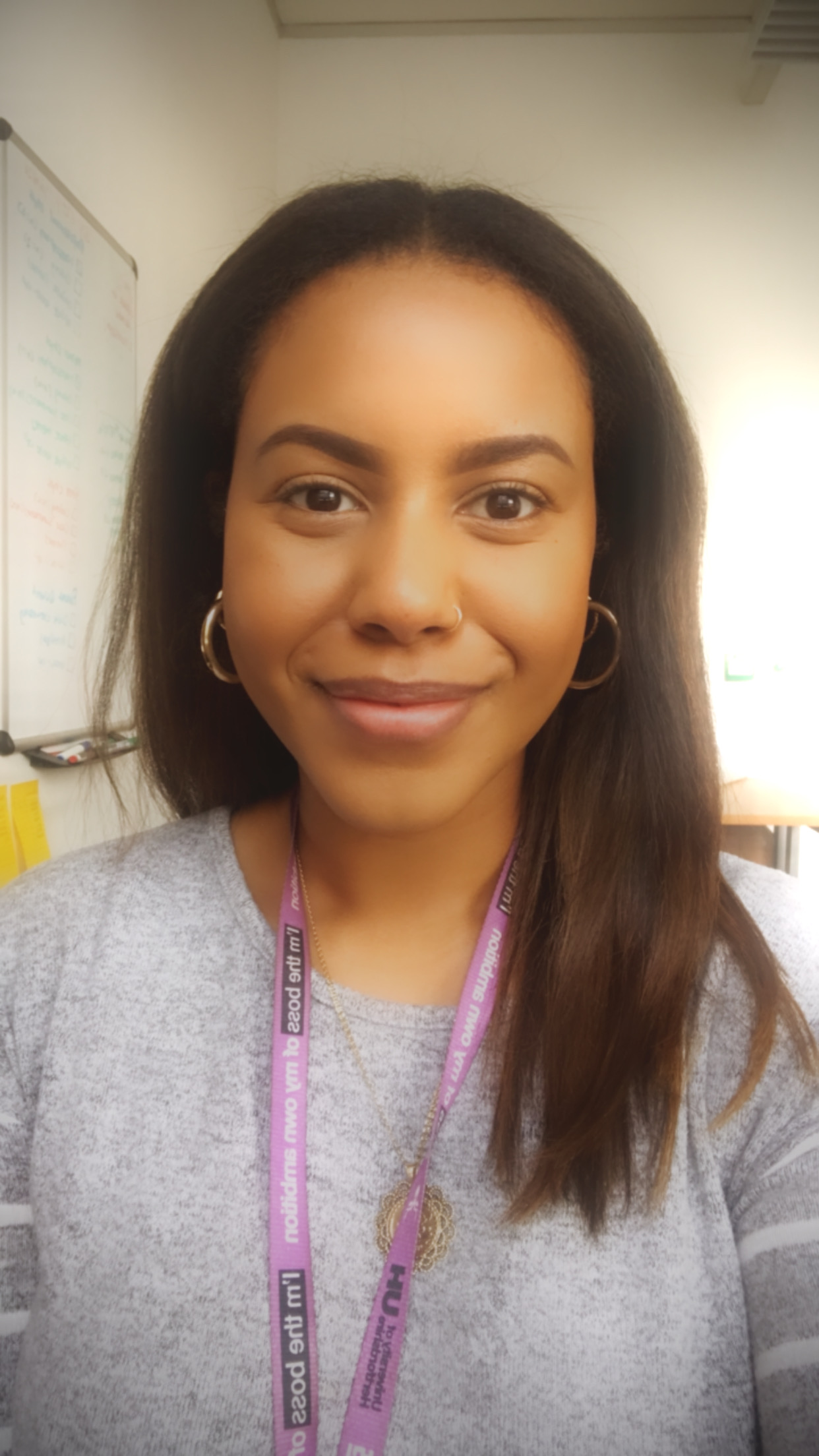 Evie, a young caramel complexion woman smiles while looking directly into the camera. Her dark brown hair rests on her right shoulder. She is wearing gold jewellery (earrings, nose ring and necklace). She is also wearing a purple University of Herefordshire a lanyard. The background is blurred, with a whiteboard to her left.