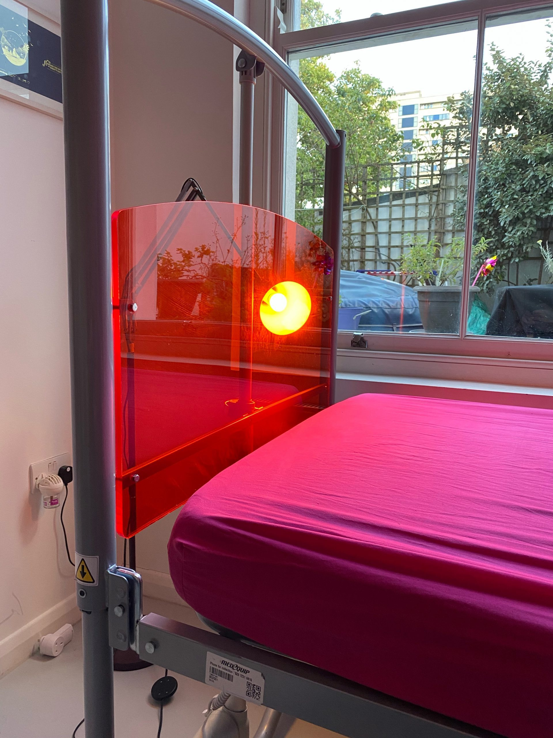 Photograph of the end of Touretteshero's new bed head. It is made of coloured amber perspex and a light is shining through it. There is a fuchsia pink sheet on the bed.