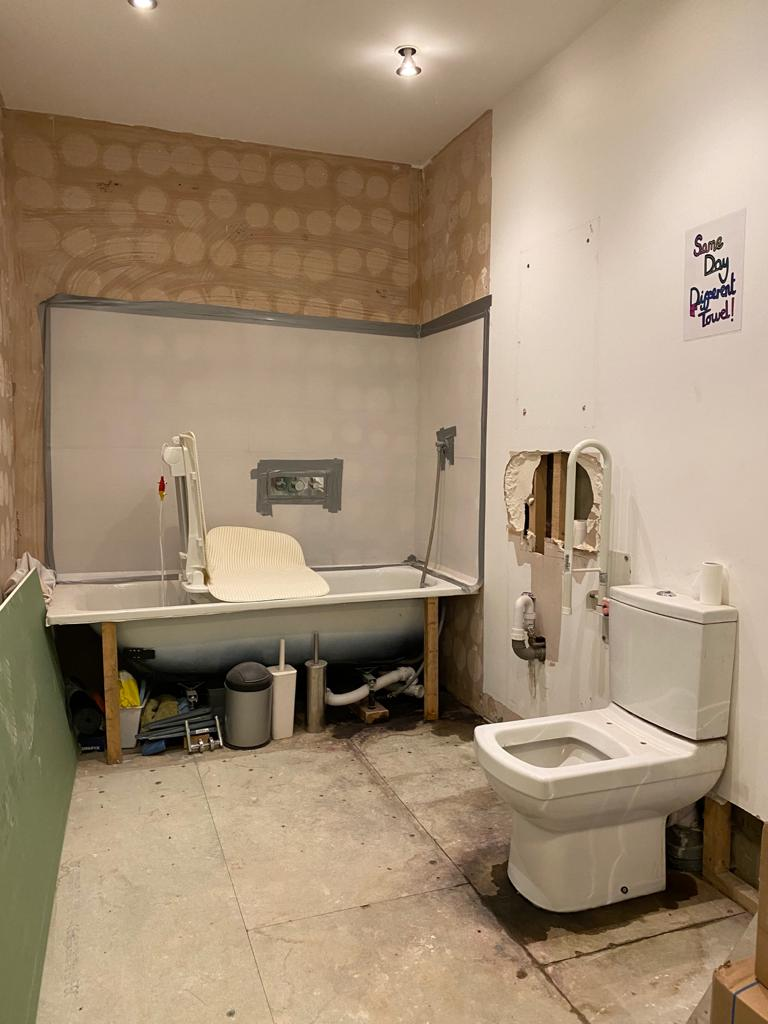 A photograph of Touretteshero's bathroom works in progress. The space is clear on either side of the toilet which enables it to be side transferred onto. The sink has been removed which used to be to the left of the toilet. There is a hole in the dry wall where the sink used to be and some pipes are visible. The floor has been stripped, as well as the back wall in the corner where the bath is installed. The bath's side covering has been removed and there is an accessible bath lift in the bath.