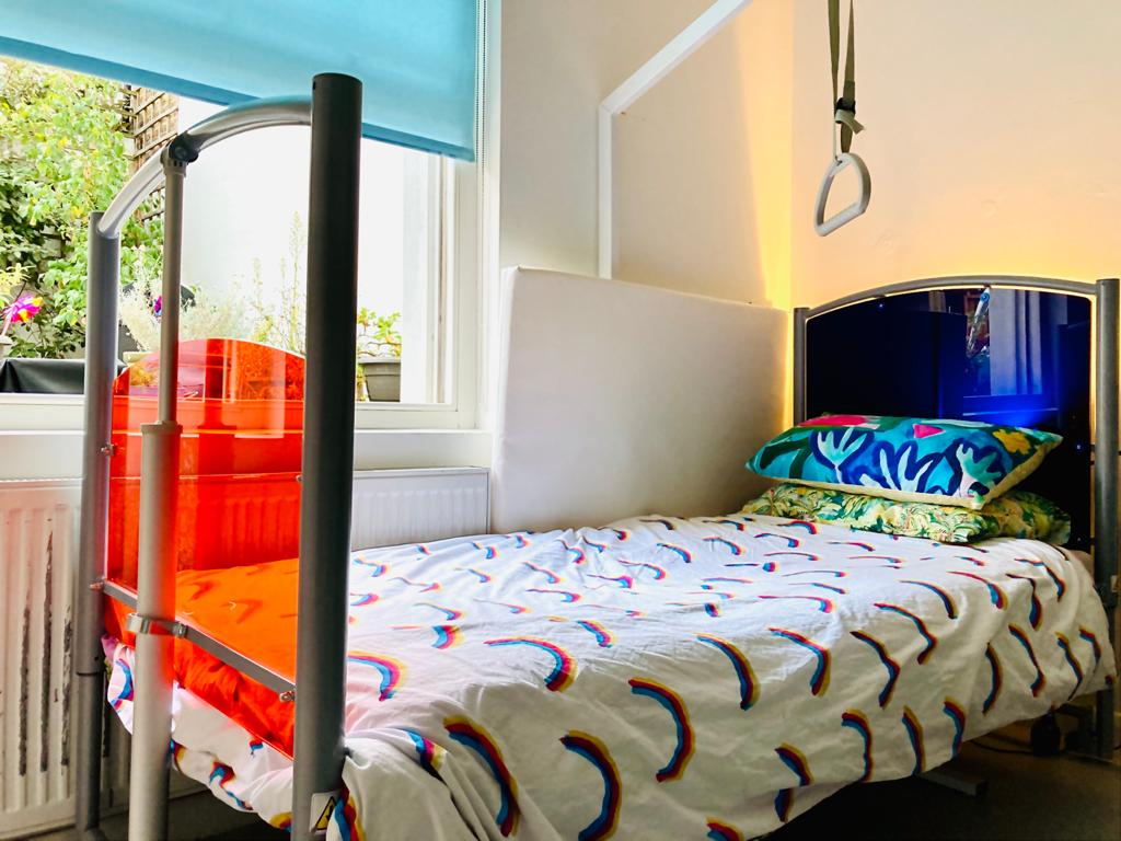 A photograph of a hospital style bed with bright orange perspex at the foot end and dark blue perspex at the head end. A white bedspread covered in mini rainbows. Light from a window shines through the perspex.