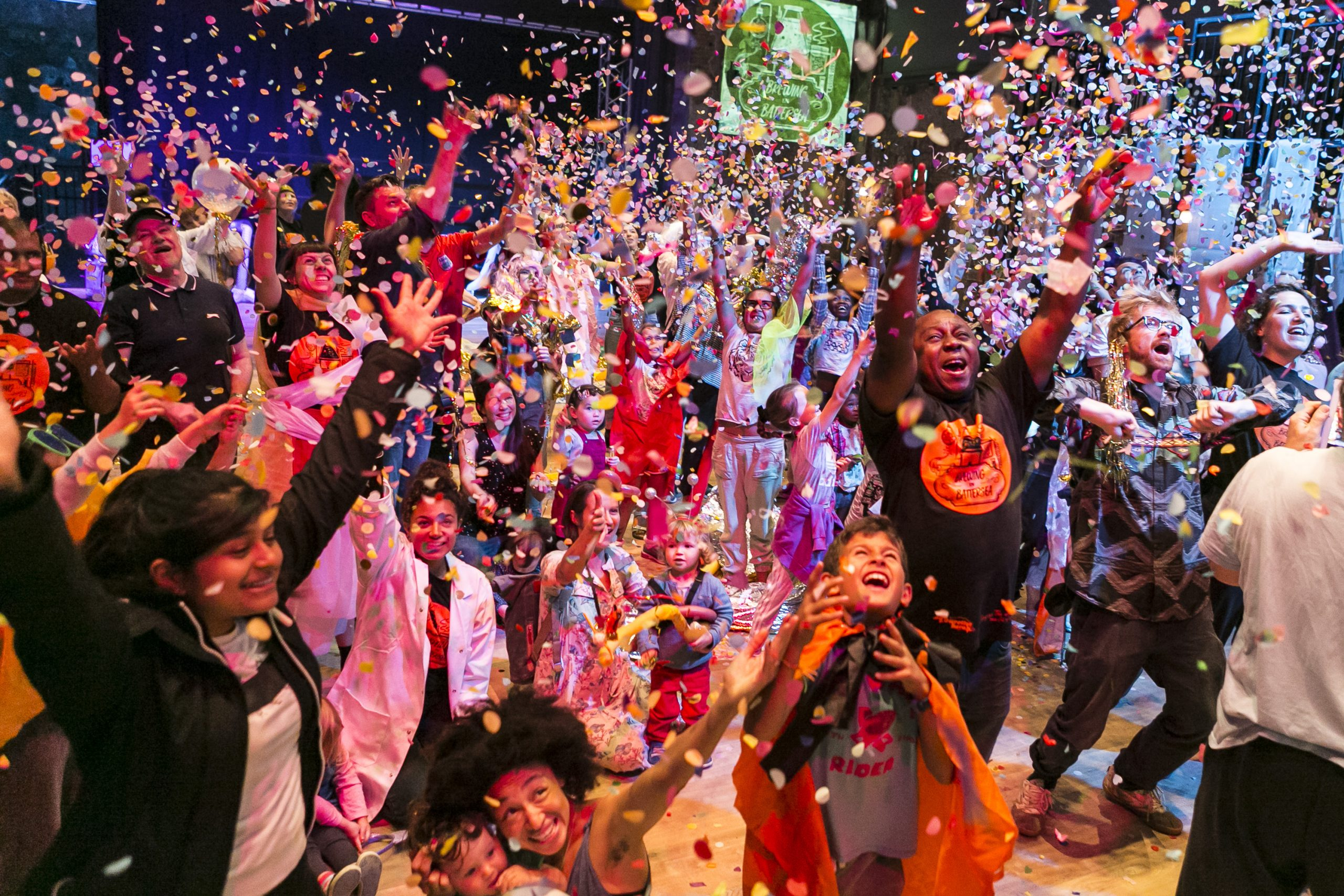 A photograph of David Ogwe in a large group of young people and adults at Touretteshero's Brewing in Battersea event the moment a confetti canon has gone off. David, along with everybody else in the photograph are smiling and cheering with both arms in the air.