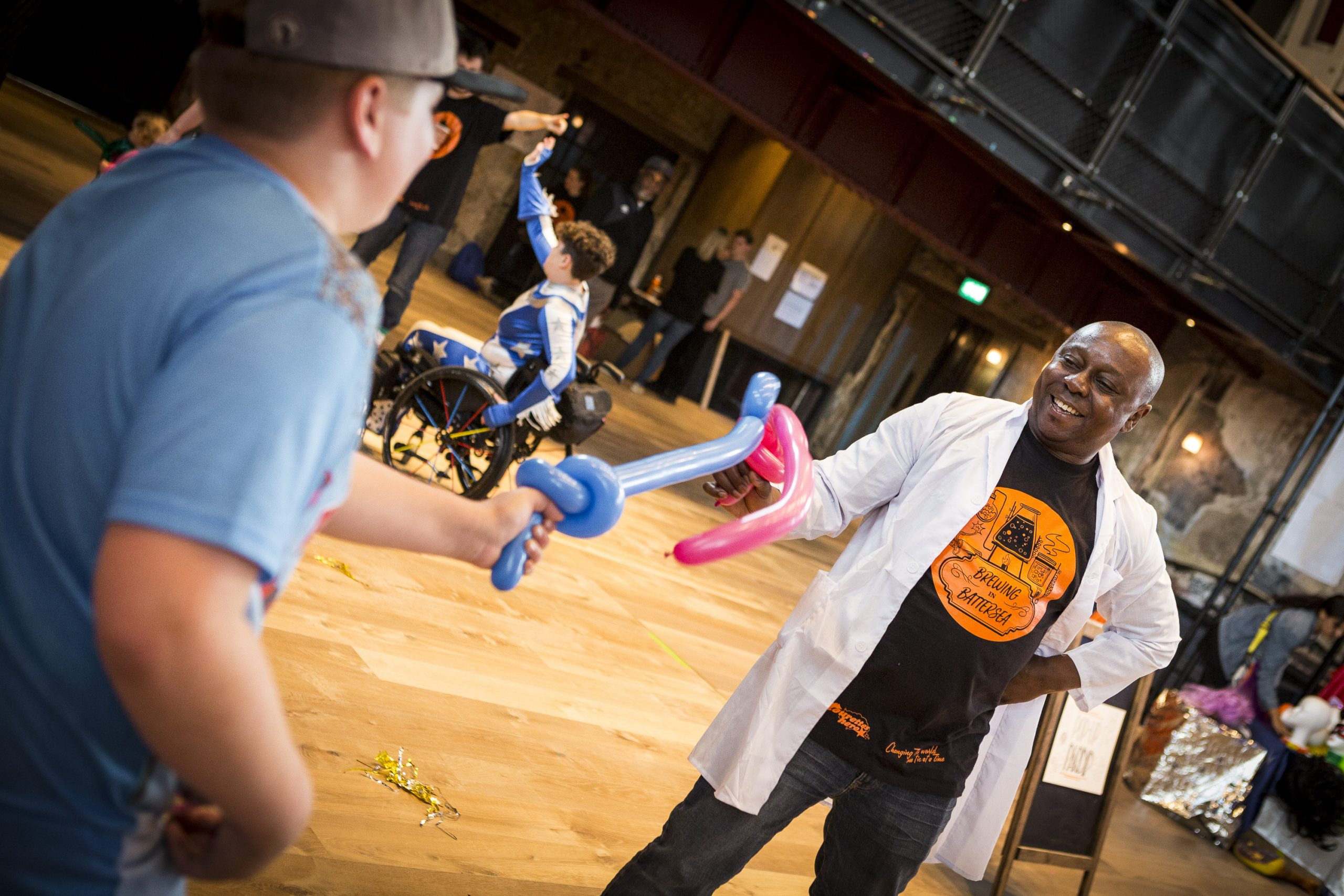 A photograph of David Ogwe sword fighting a young person with balloon swords at Touretteshero's Brewing in Battersea event in the Grand Hall in Battersea Arts Centre. David is smiling with one hand on his hip and the other hand brandishing a pink balloon sword. He is wearing a white lab coat and a black t-shirt with an orange 'Brewing in Battersea' graphic. The young person is wearing a flat back hat and blue t-shirt. Touretteshero can be seen in the background of the picture in her blue and white superhero costume. She is sitting in a black wheelchair with multicoloured spokes.