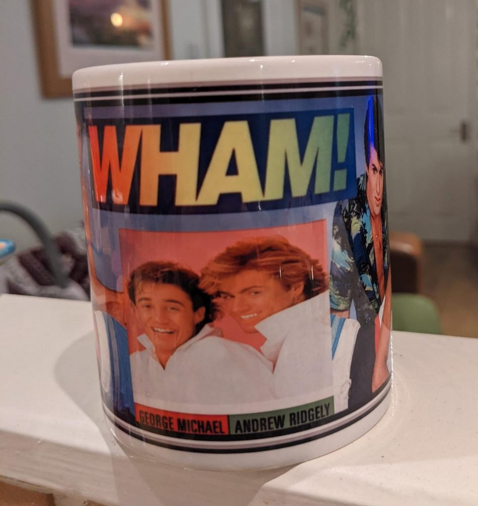 A photo of a Wham mug, it's a rainbow of colours with a photo of the pop group WHAM on the side.