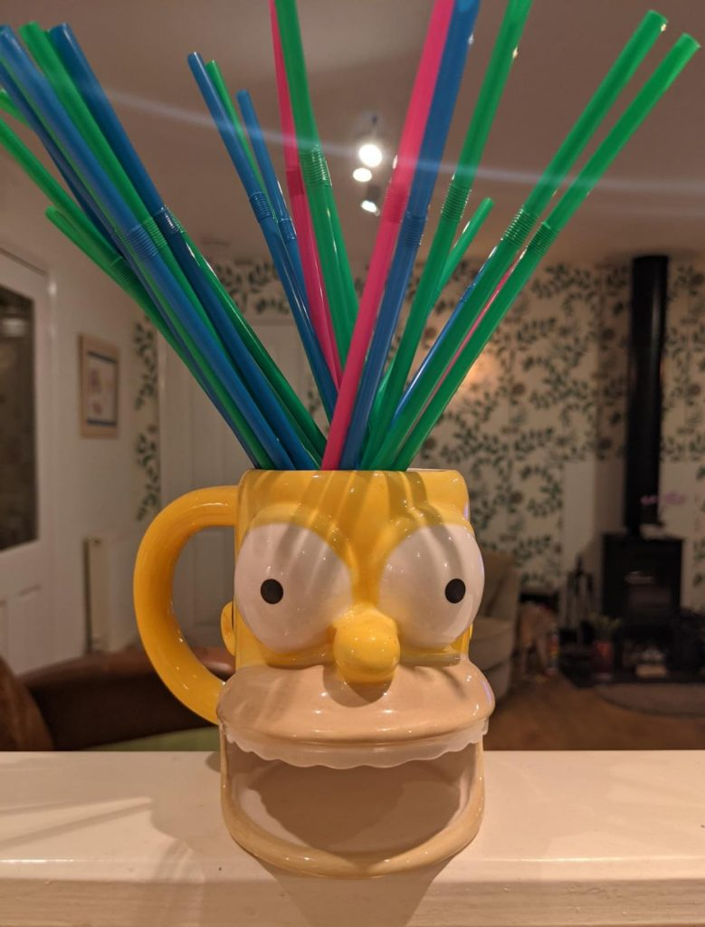 A photo of one of Katie's ugly mugs - this mug is shaped like homer Simpsons head, with bulging eyes, a big grin and a handle on one side. Colourful straws are in the cup and burst out of the top of Homer's head.