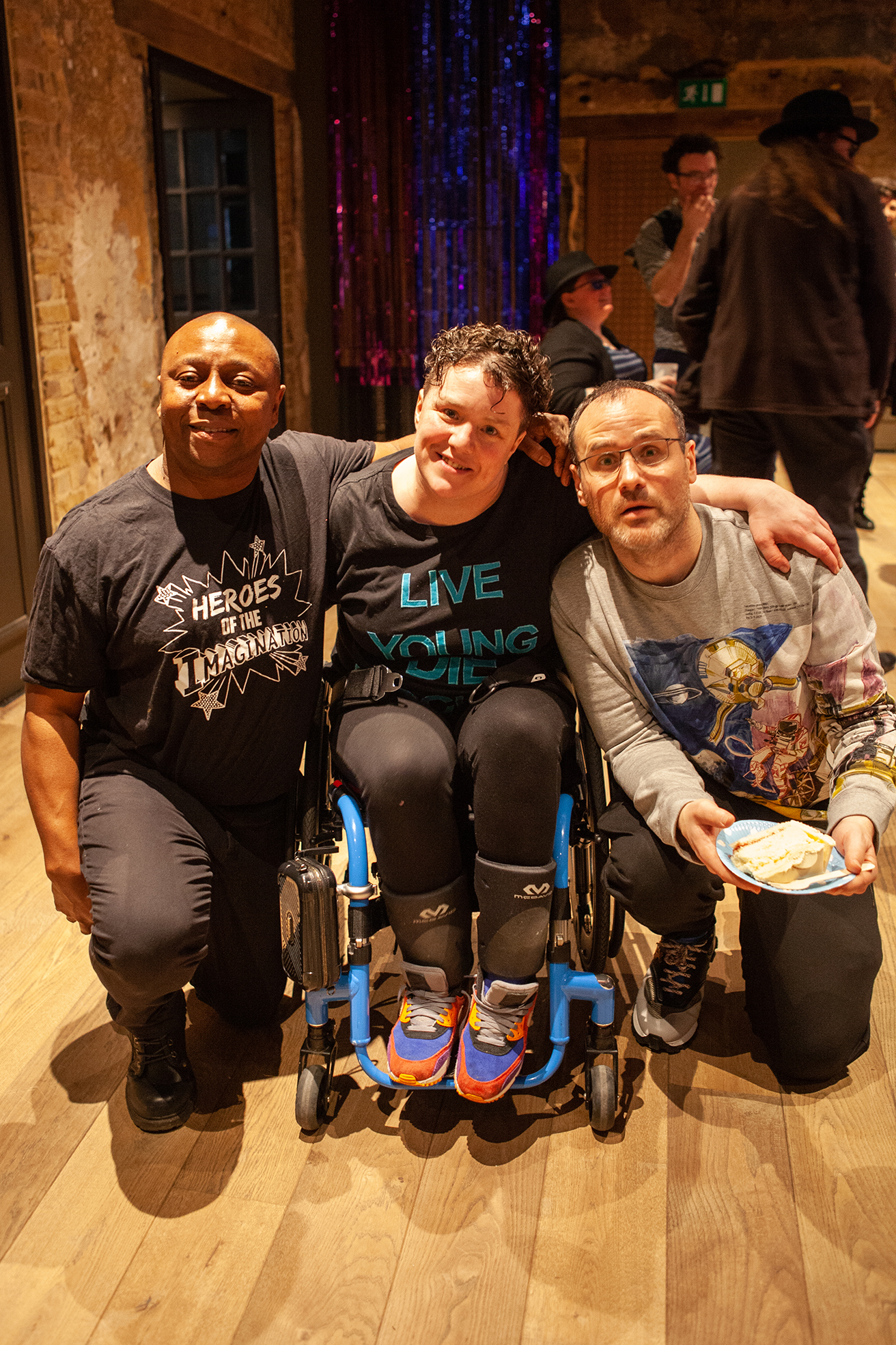 A photograph of David Ogwe, Touretteshero and Leftwing Idiot at Touretteshero's 10th Birthday party at Battersea Arts Centre. David is smiling on one knee to the left of Touretteshero and has his arm around her. Touretteshero is smiling and sat in between David and Leftwing Idiot with her arms around both of them. Leftwing Idiot is kneeling on one knee holding a piece of birthday cake.