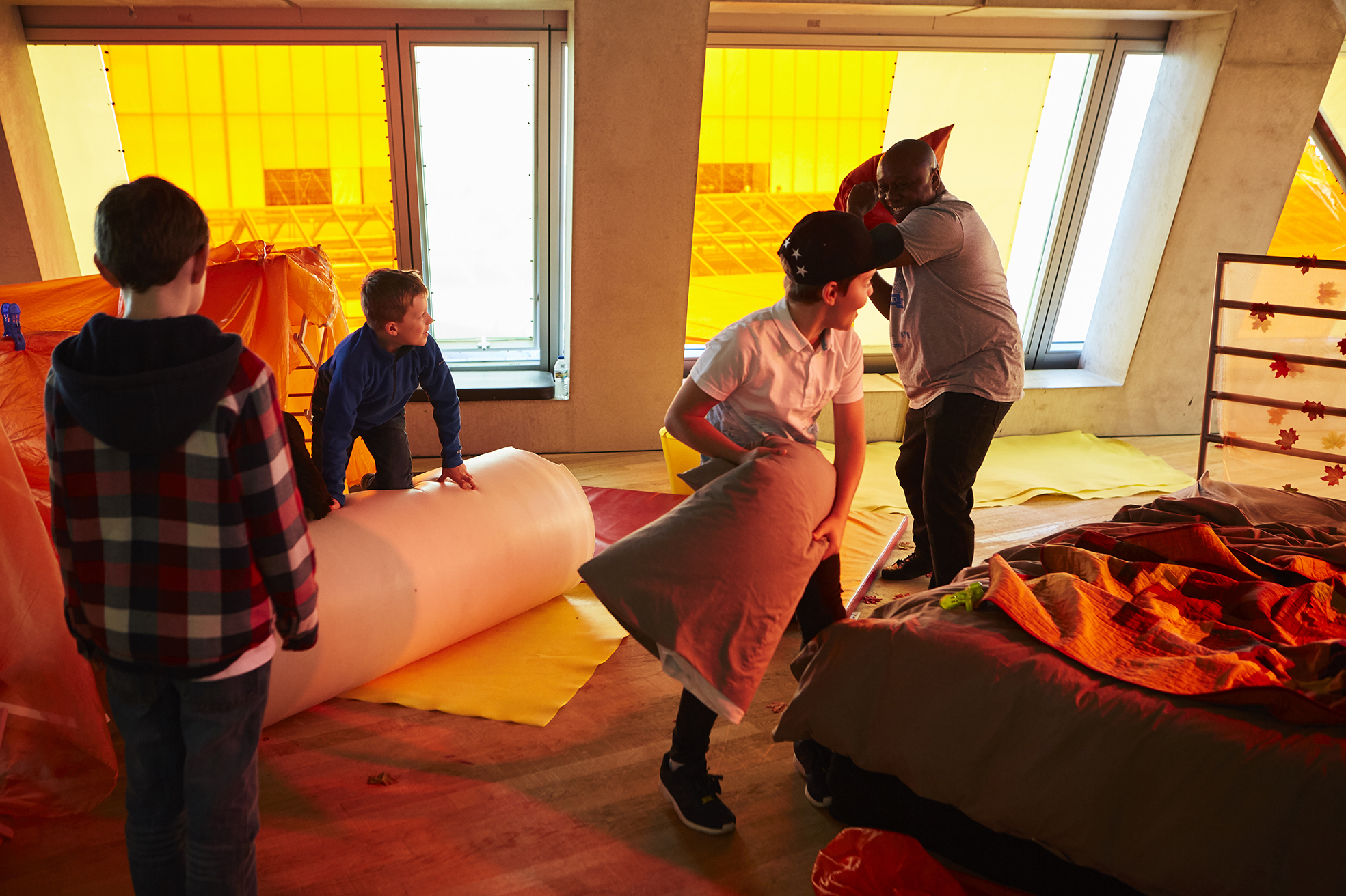 A photograph of David Ogwe with a group of young people at a Touretteshero event at the Tate. David is smiling and having a playful pillow fight with another child. Two children look on. The floor is strewn with blankets and bean bags.