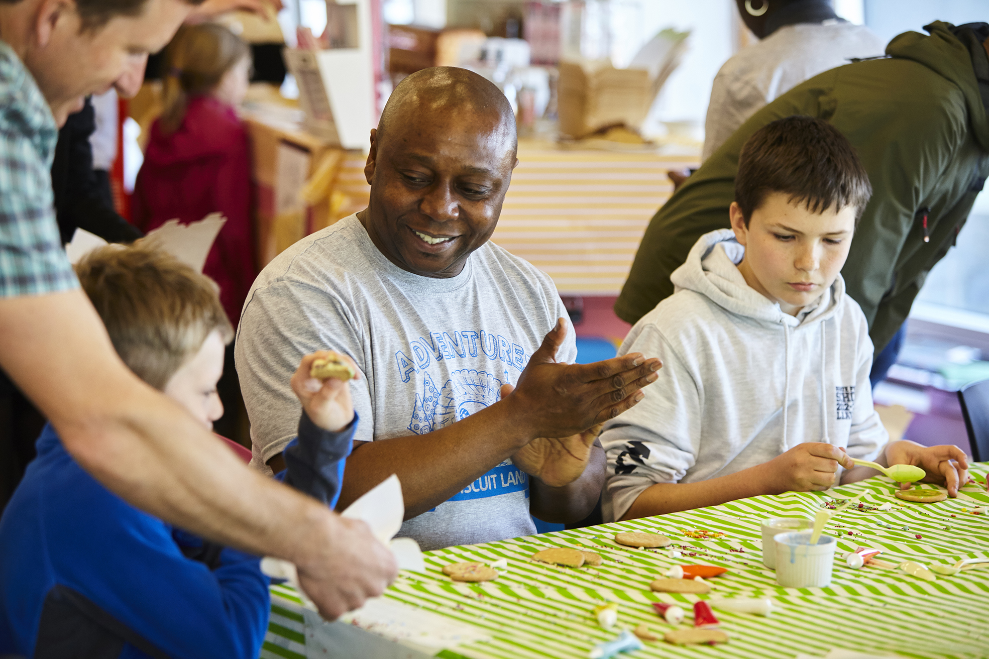 A photograph of David Ogwe sitting at a table with two young people at a Touretteshero event at the Tate. The table is covered with a green and white striped tablecloth and has biscuits, different coloured icing tubes and other cake decorating items. David is smiling and facing a child to his right who has just taken a bite out of his biscuit that he has decorated. The other child to David's right is decorating a rich tea biscuit with bright green icing.