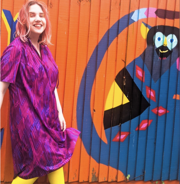 Katie, a white person in her early twenties, is standing in front of a bright orange wall with a colourful monkey painted on it. Katie has pastel pink hair and is wearing a bright purple dress with yellow tights. She is smiling.