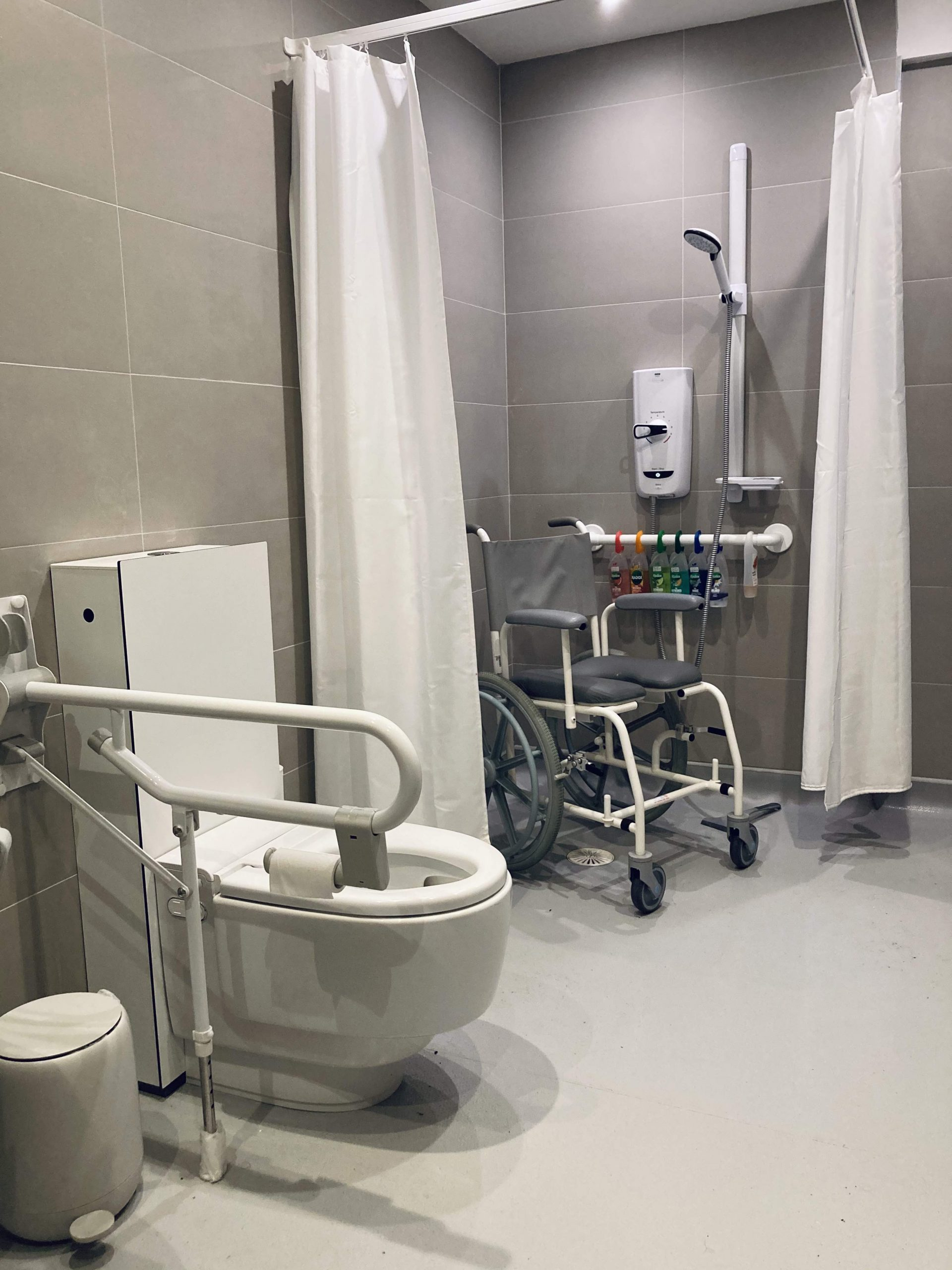 A photograph of part of Touretteshero's newly renovated accessible wet-room bathroom. The walls are tiled in large rectangular slate-grey tiles. These are laid horizontally floor to ceiling. White shower curtains are pulled open to either side of it's right angled rail. A shower chair sits in the corner sits next to the shower unit and showerhead. Below it is a grab rail with many multi coloured shower gels hanging from the rail. A sink hole can be seen beneath the shower chair whiA wash and dry geberit toilet is in the left foreground of the image with a grab rail to it's right.
