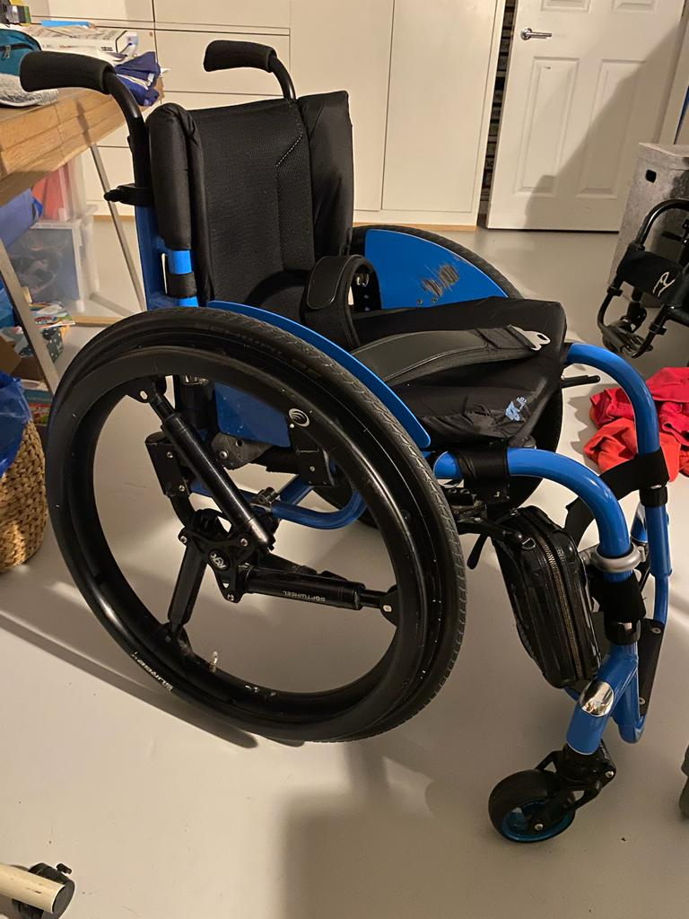 A photo of a blue framed wheelchair, which has a black seat, black seatbelt and black wheels. On the front of the frame is a small rectangular wheelchair bag.