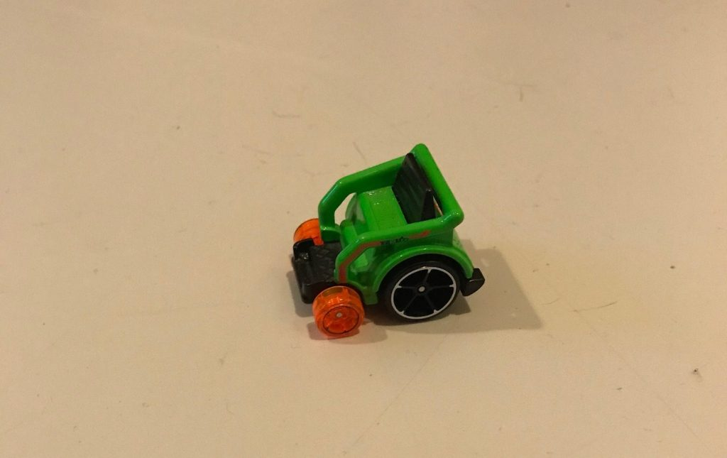 A photo of a small spinny wheelchair toy. It is green with large black wheels at the back and small orange wheels at the front.