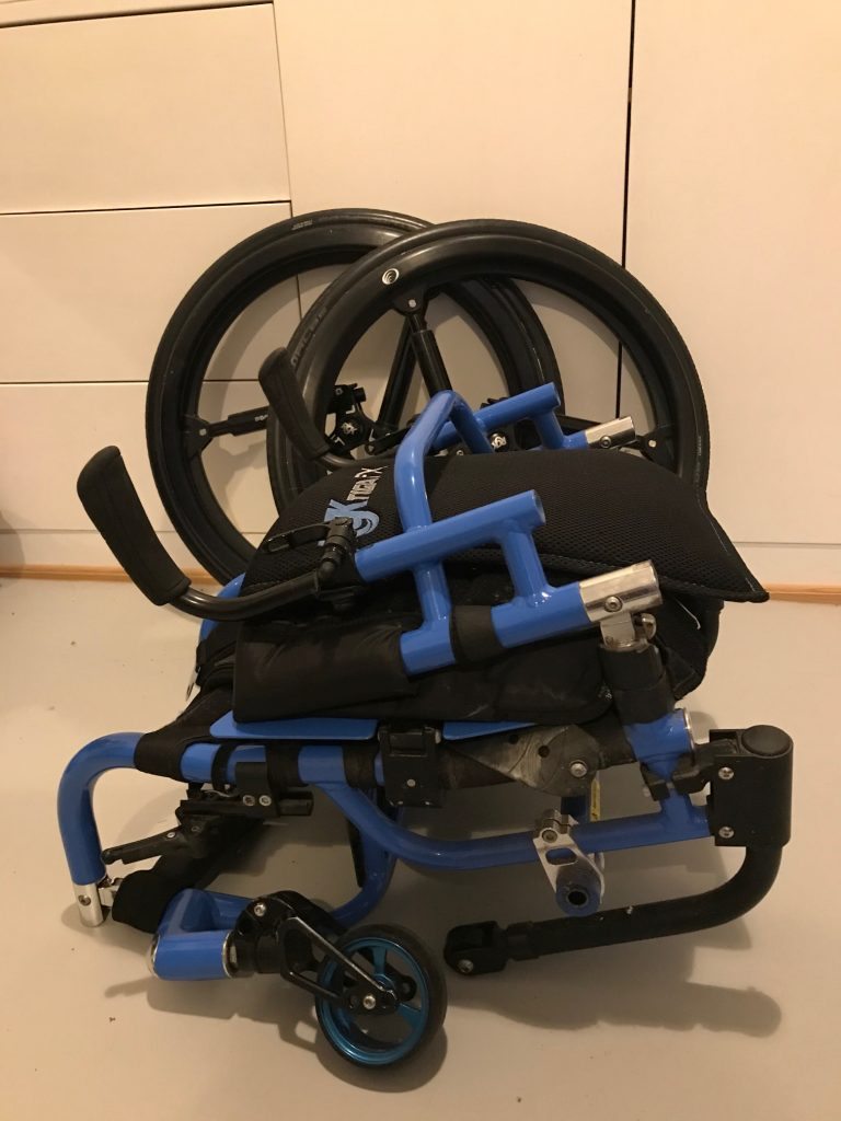 A photo of a blue folded wheelchair, with the wheels removed in the background.