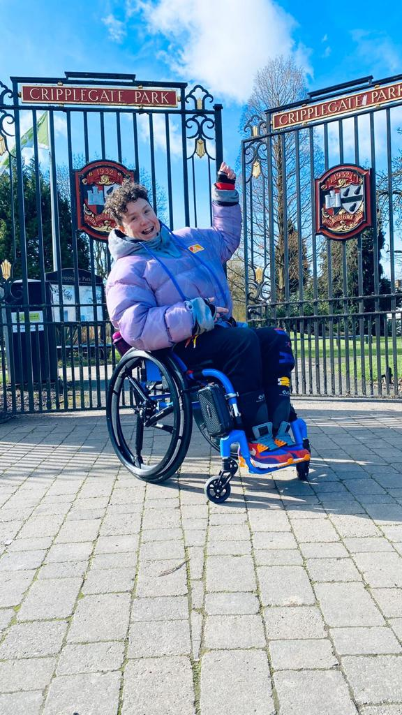 A photo of Jess sitting in her wheelchair with shock absorber wheels. She is wearing a cool purple puffy jacket and bright multi-coloured trainers. She is in front of park gates which have the signs for Cripplegate Park on them.