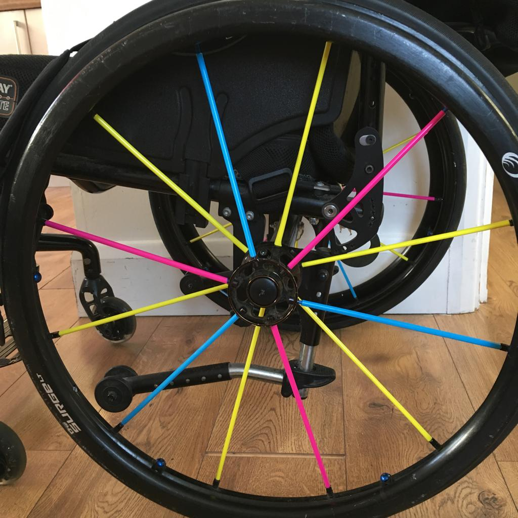 A photo of a wheelchair wheel. The spokes are brightly coloured pink, yellow and blue.